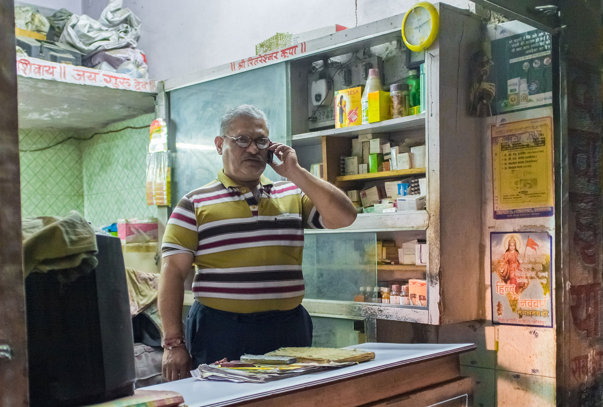 Man stands in small shop talking on phone