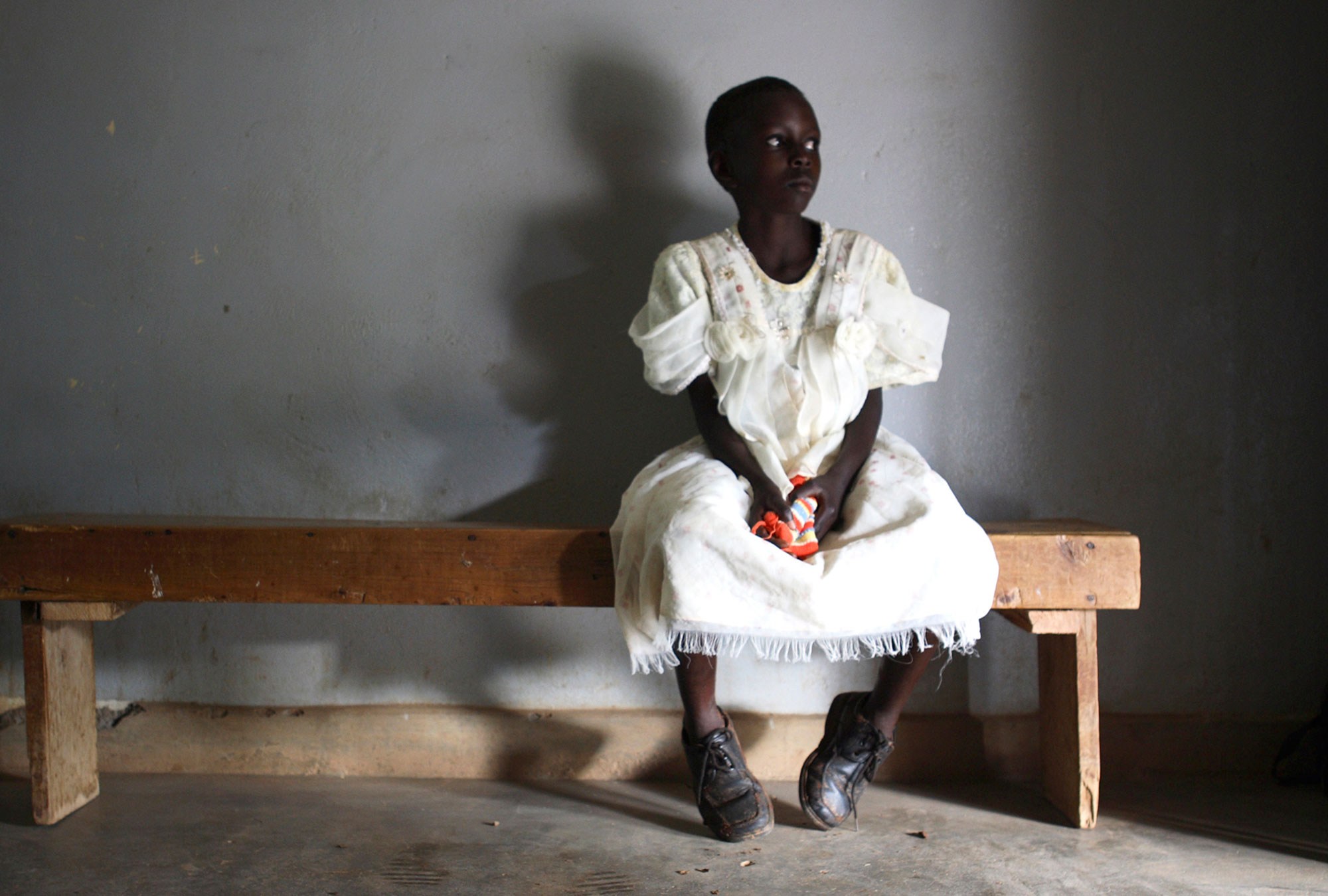 A young girl waits in a health center in Uganda.