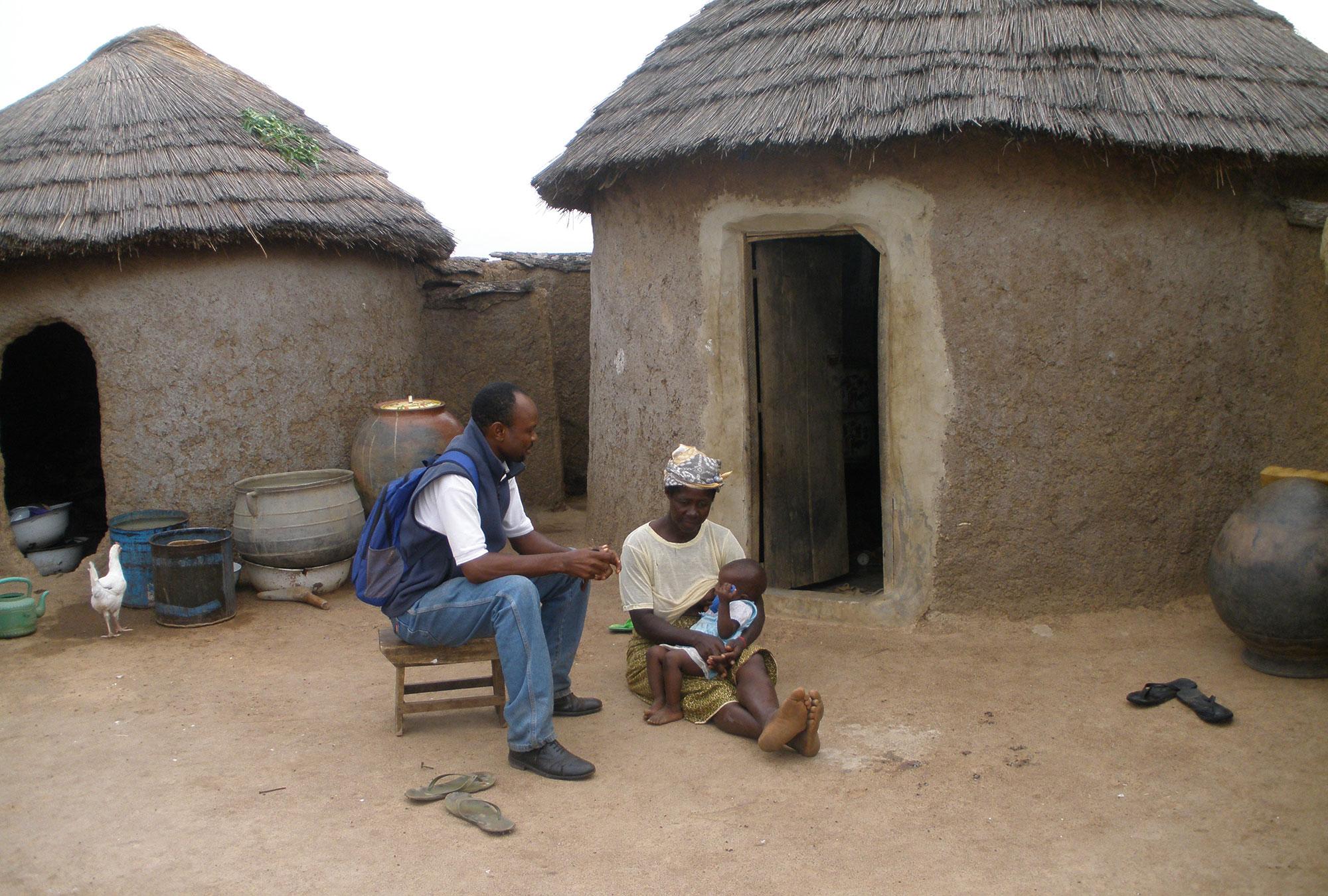 Savings client talks with surveyor in Ghana