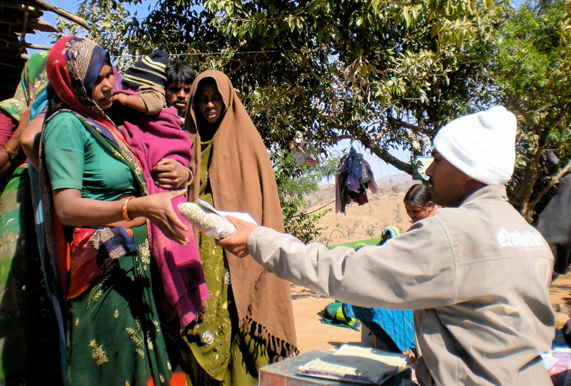 Woman receiving a kilogram of lentils as a reward for having her child vaccinated, Rajasthan, India.