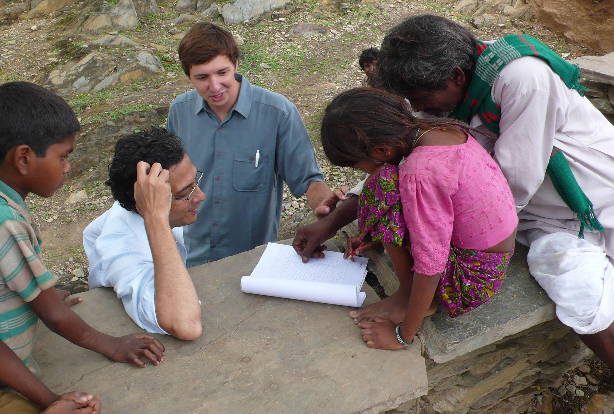 J-PAL staff help a young girl solve a maze exercise in India.