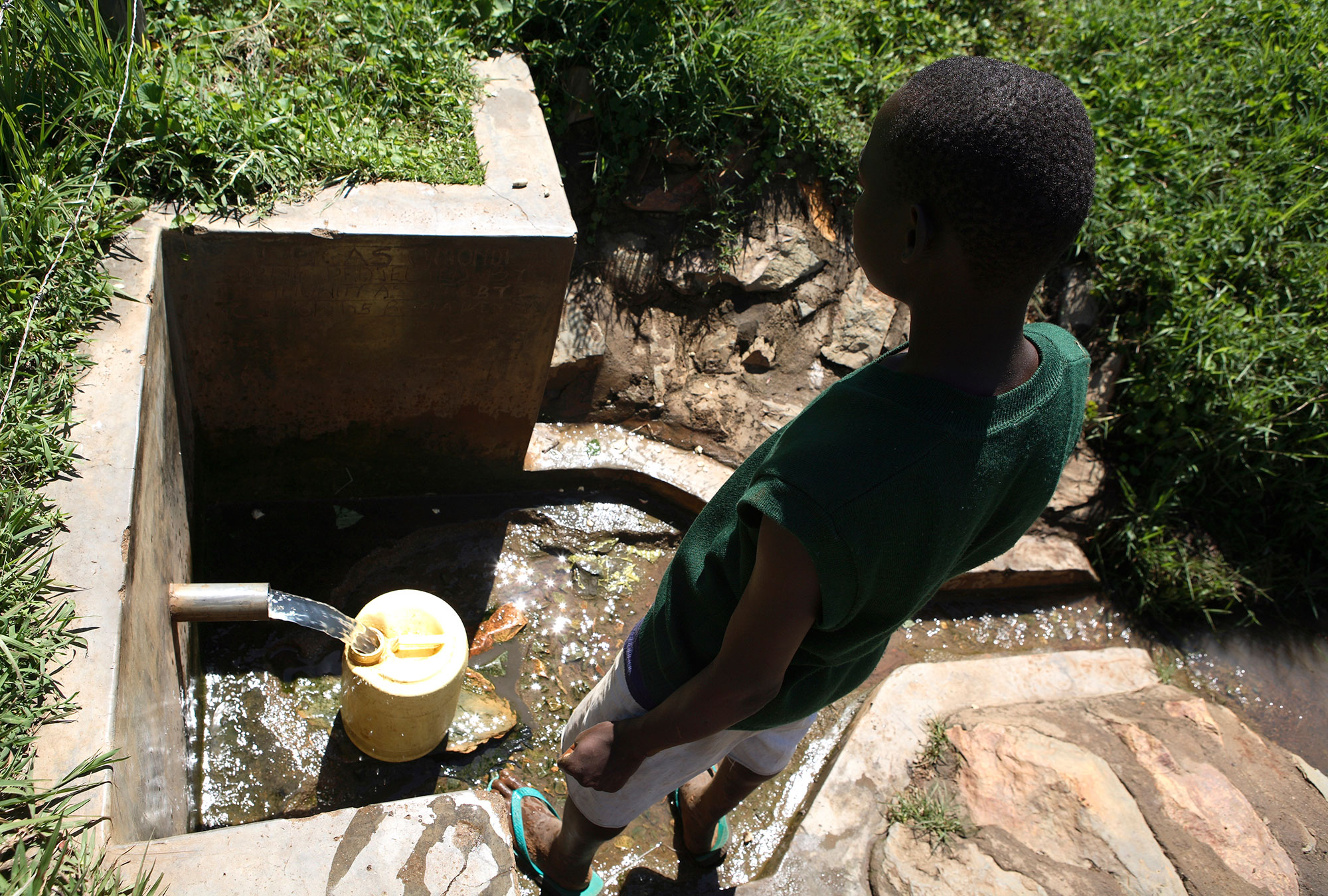 Boy watching water pour out of a concrete-encased spring.
