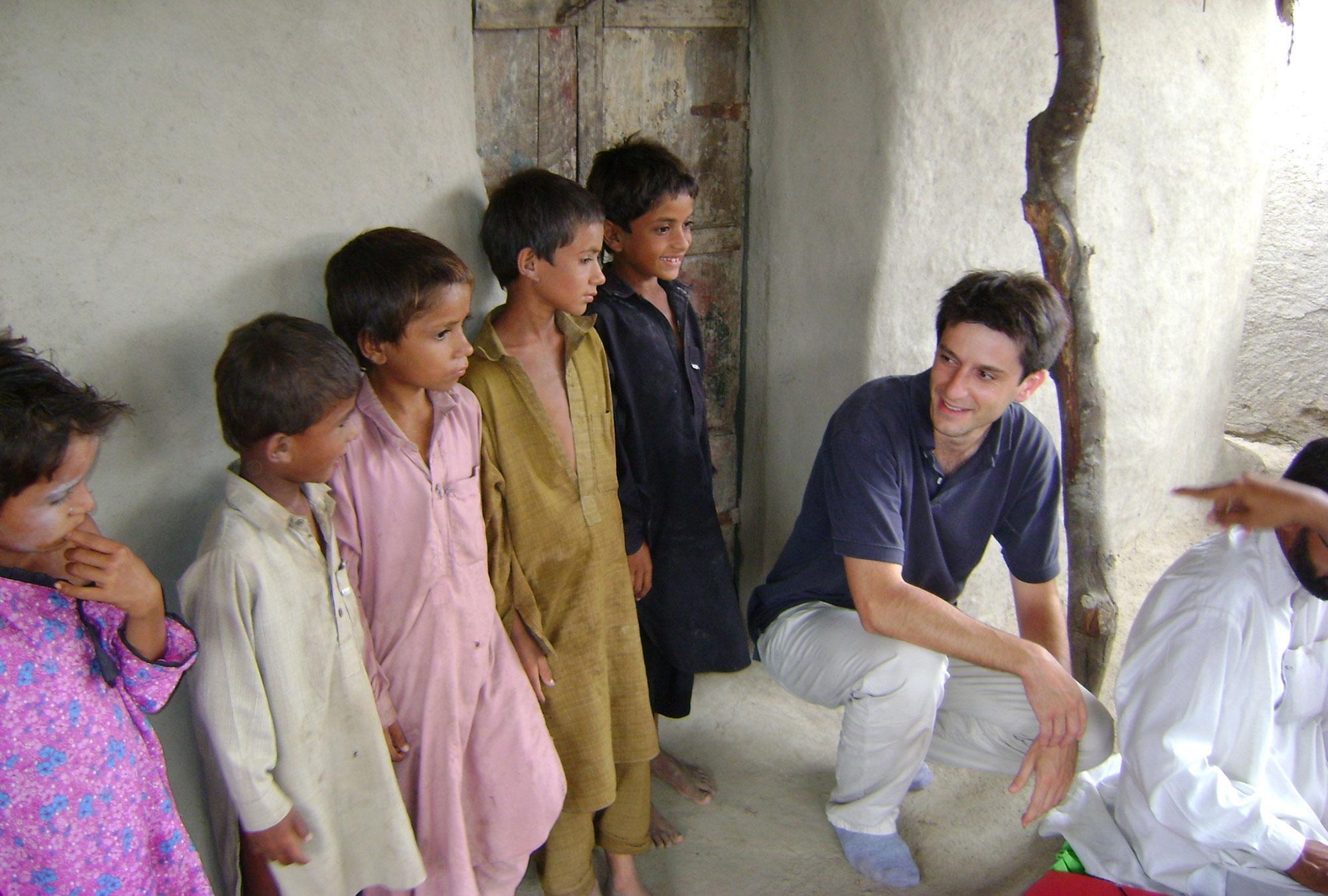 Children in shalwar kameez stand outside of mud building