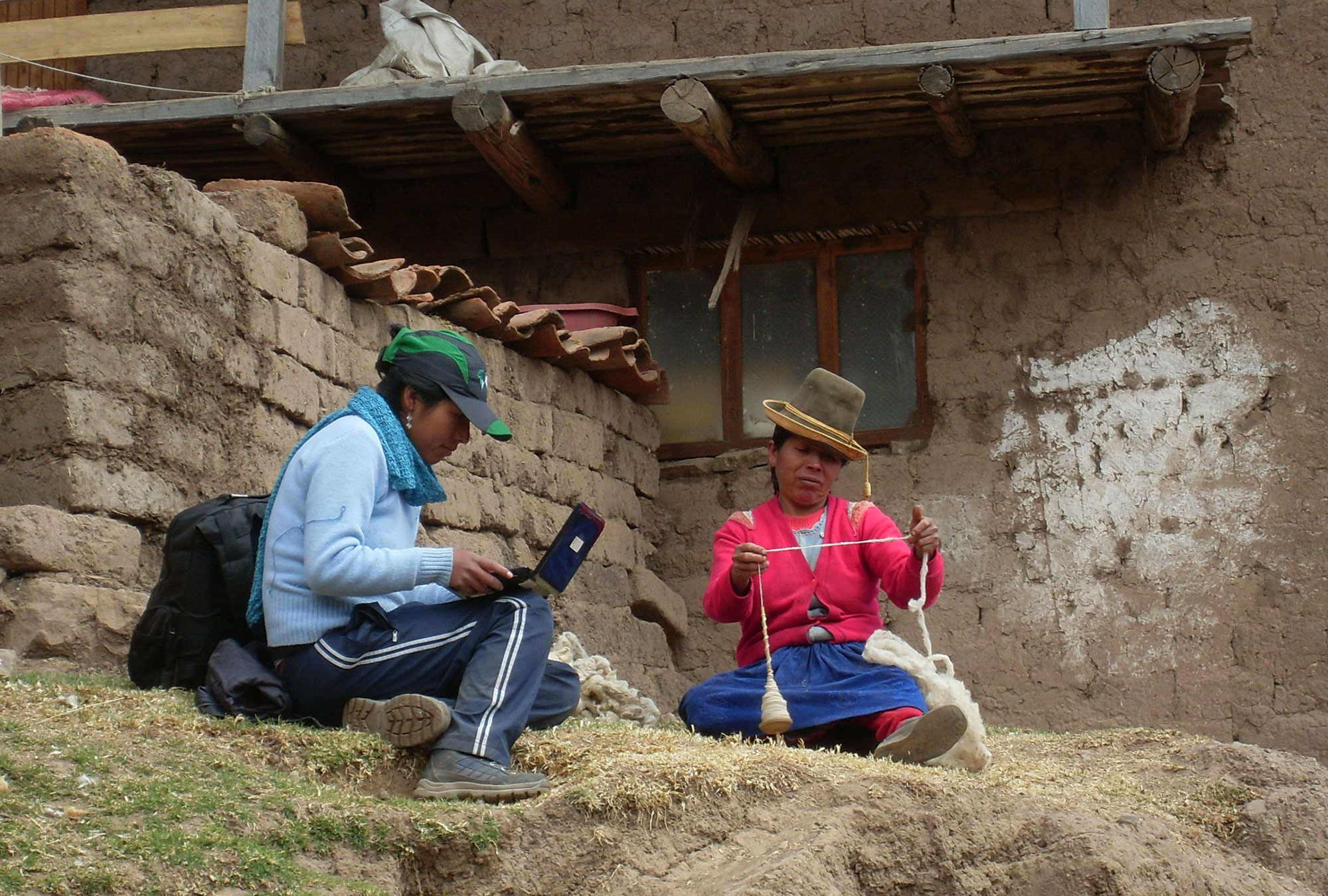 Woman on laptop talks to Peruvian woman spinning wool