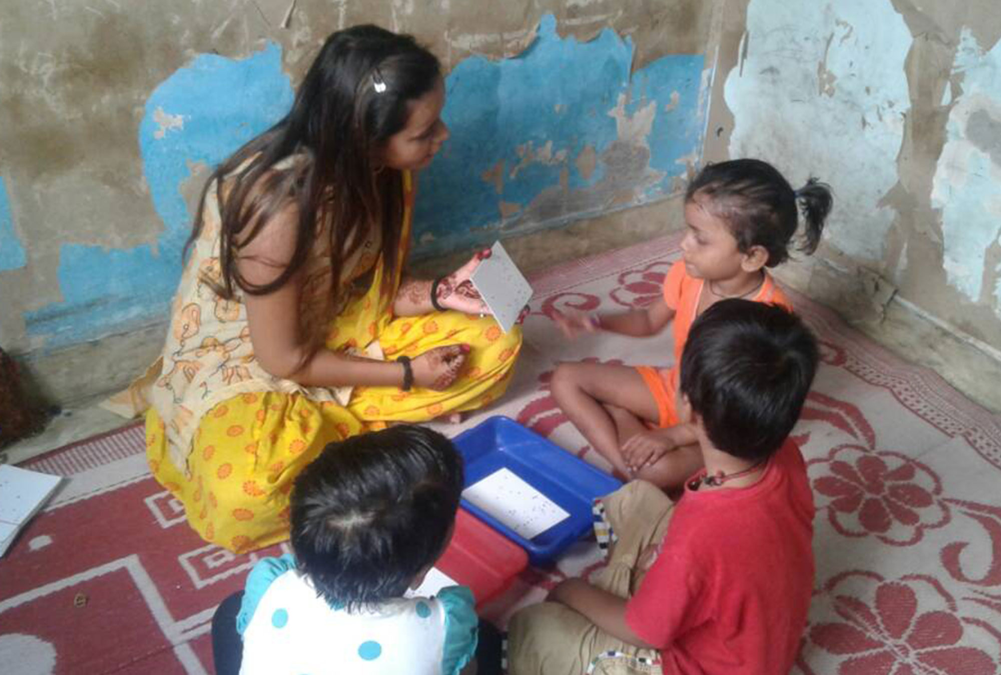 Woman sits with two kids as they play math games