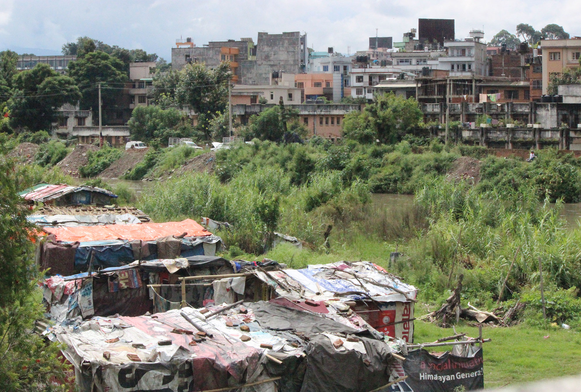 Houses made from tarps and wooden poles on the outskirts of a city