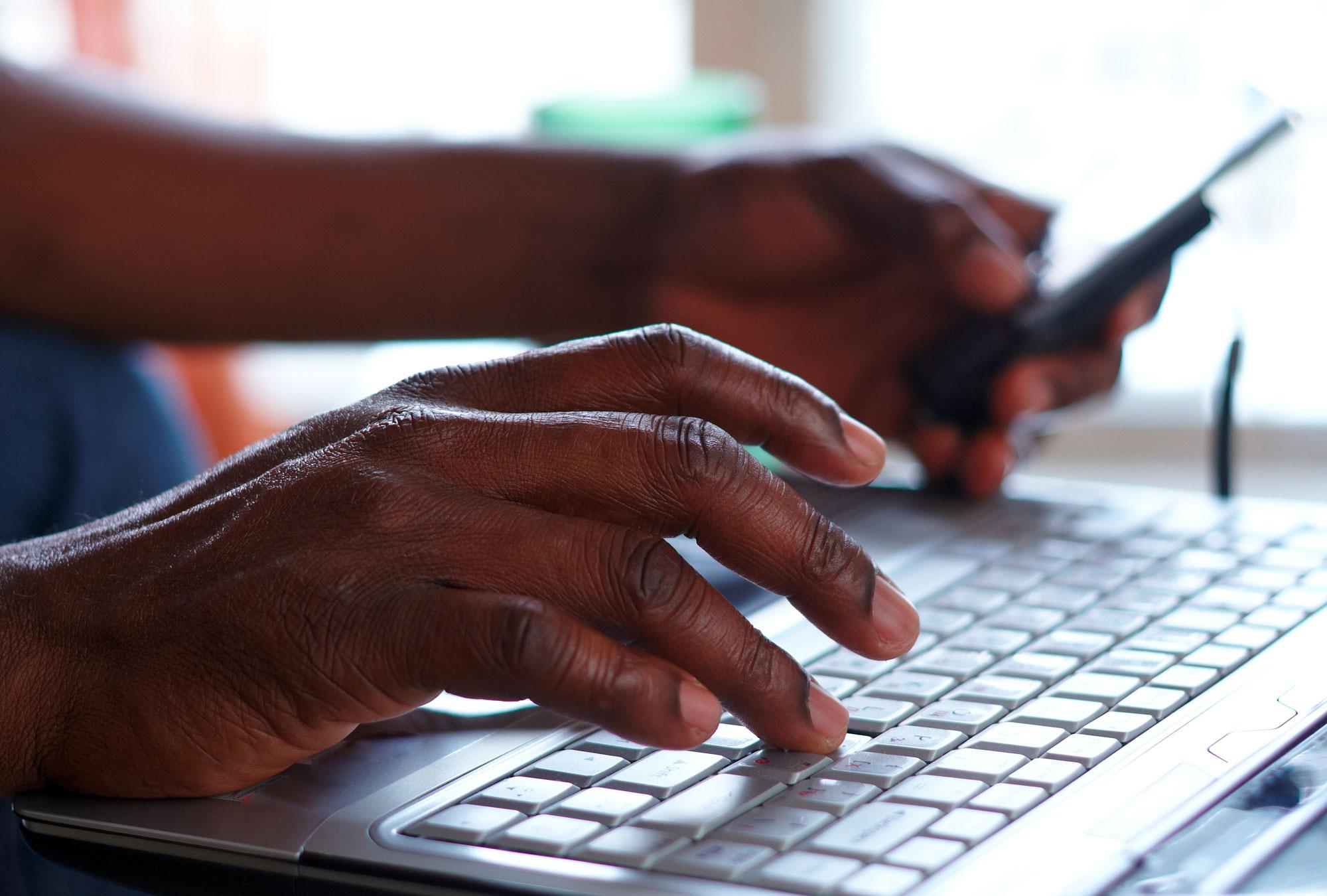 Hands type on keyboard