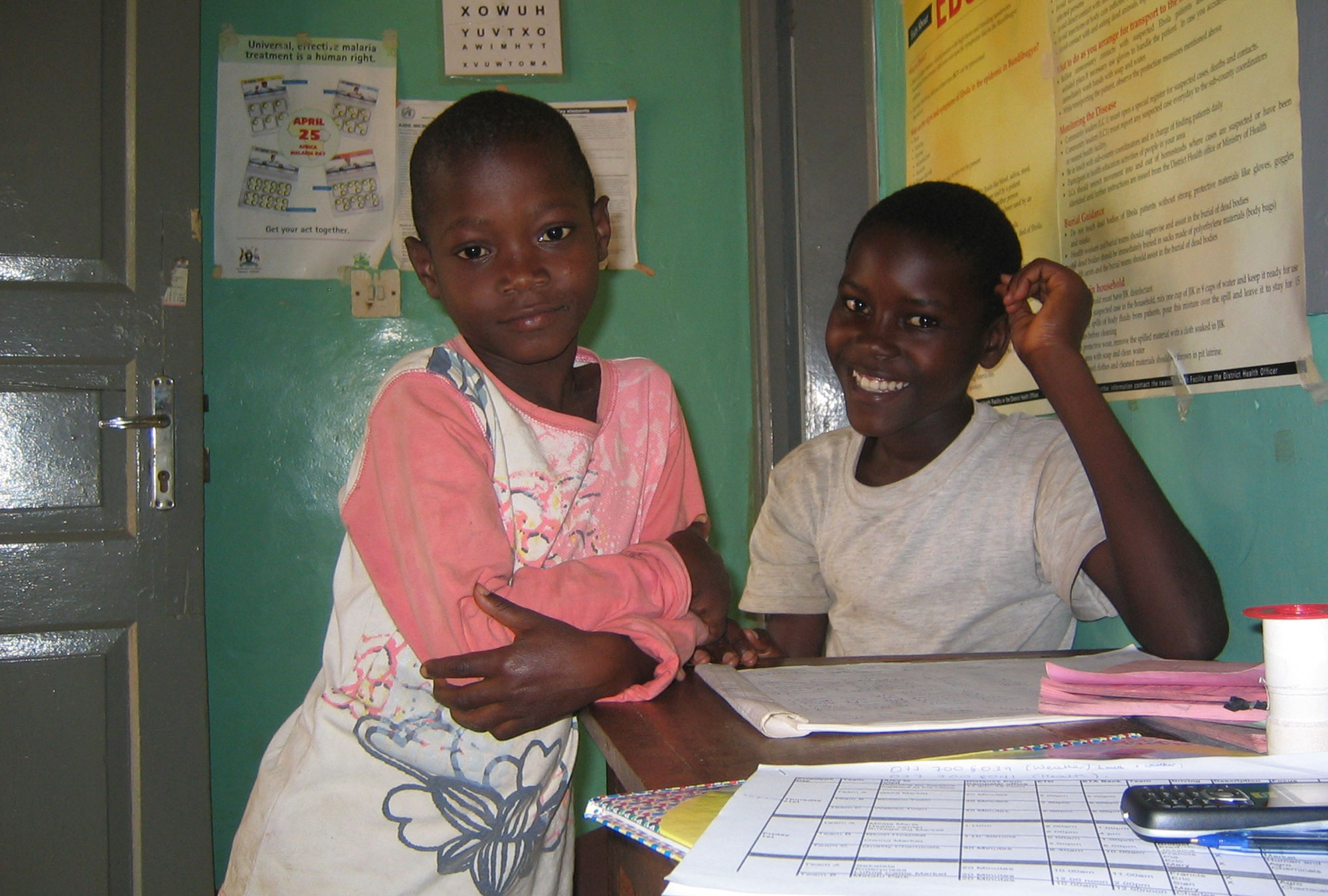 Two Ugandan boys smile in a room filled with posters