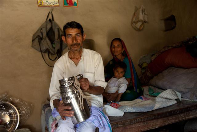 Indian man pictured with his family and his wares