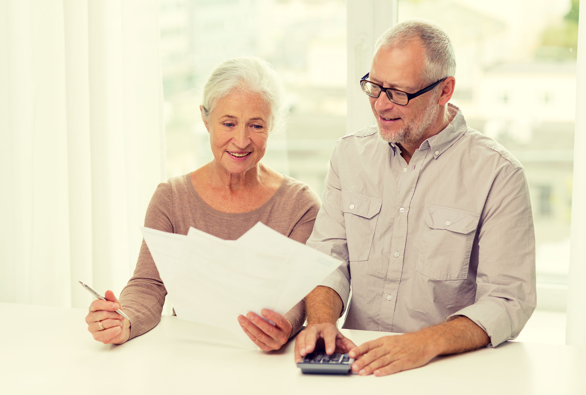 Older man and woman look at financial papers