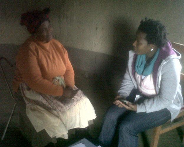 Two women in chairs talking inside house