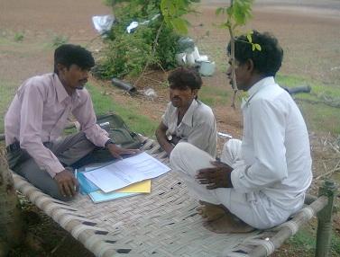 Three men talking over paperwork outdoors