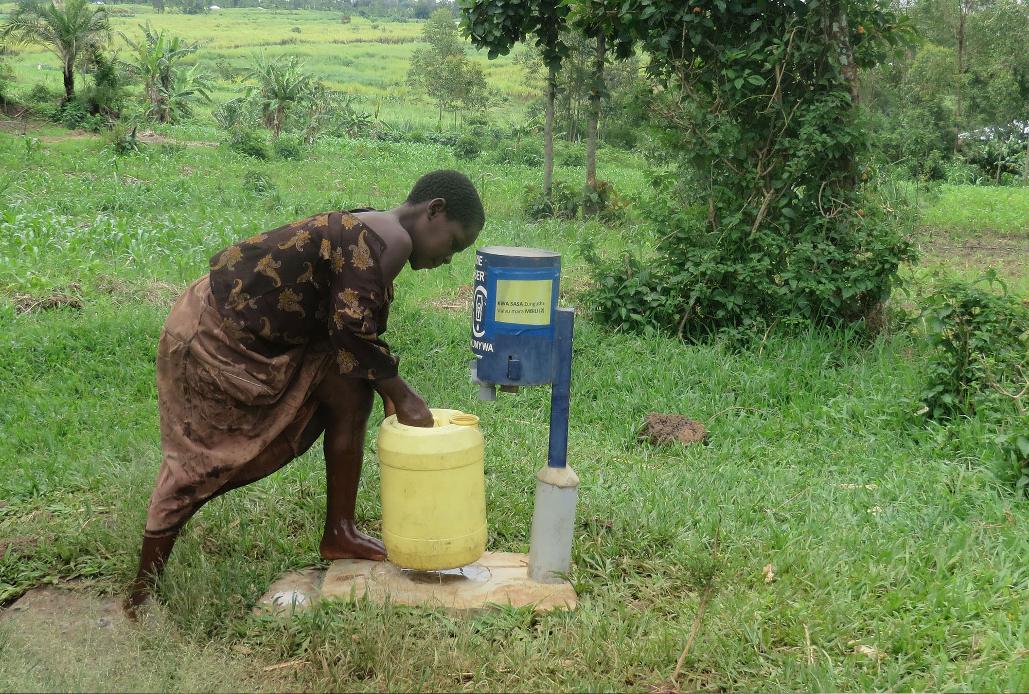 Young girl chlorinating her water at a point-of-use public dispenser, Kenya, 2015