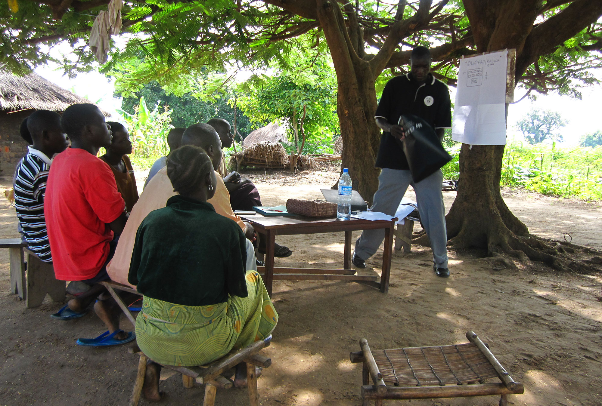 Group of Ugandan youth watch man giving presentation under a tree