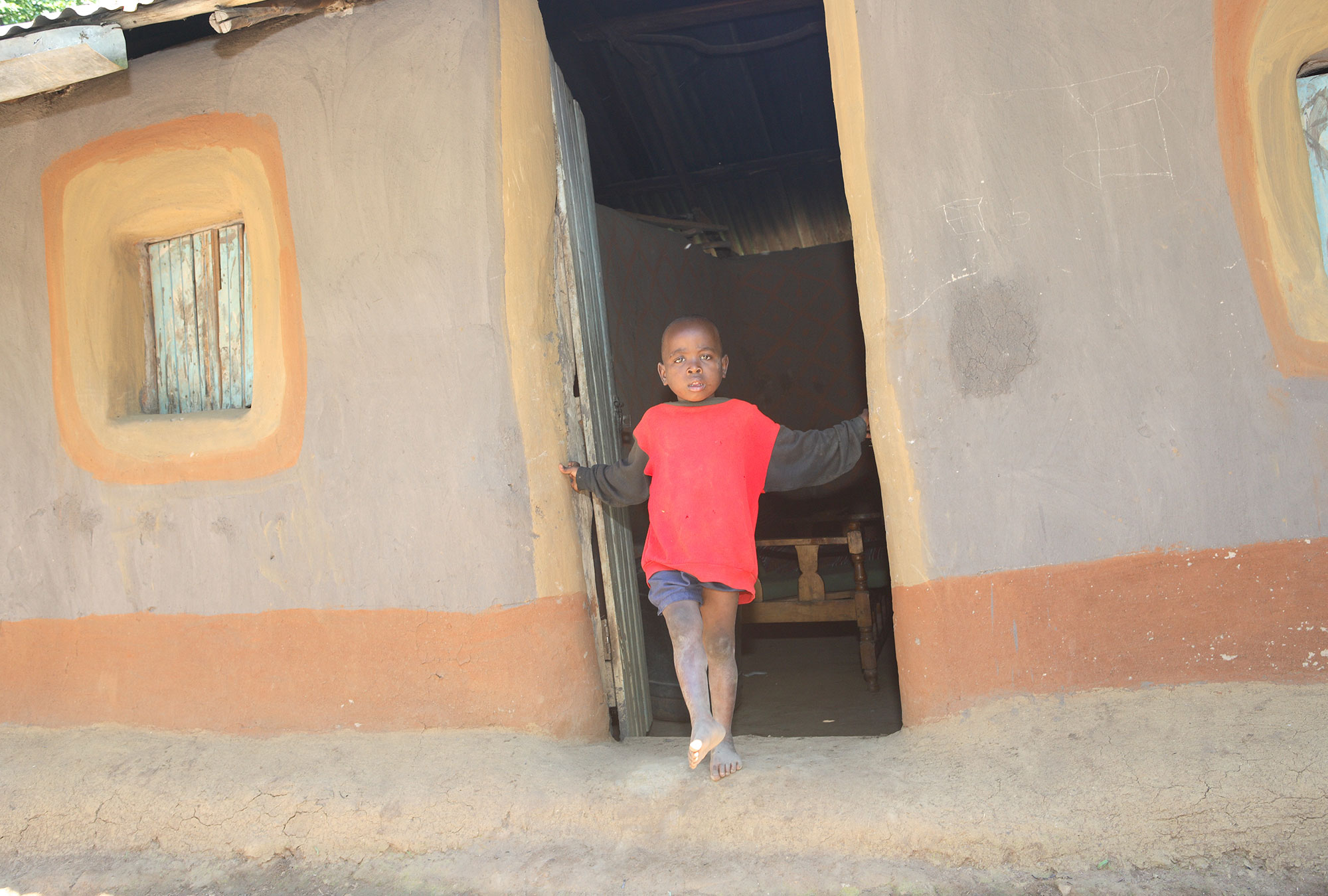 Young boy stands in doorway of house