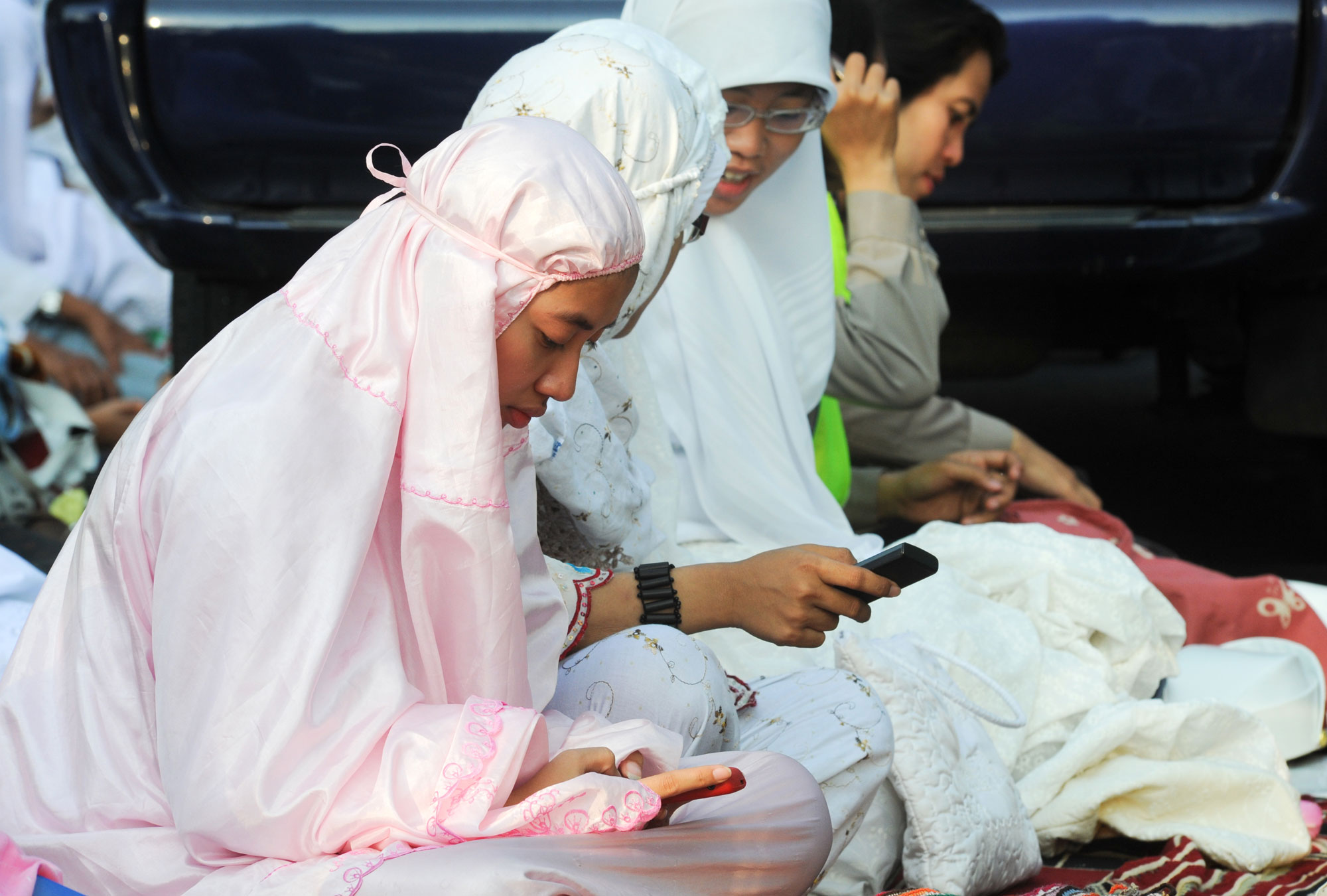 Women in hijab text on their cellphones in Indonesia