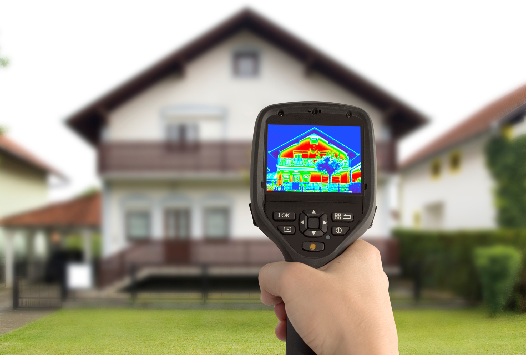 Hand holds up infrared sensor in front of house