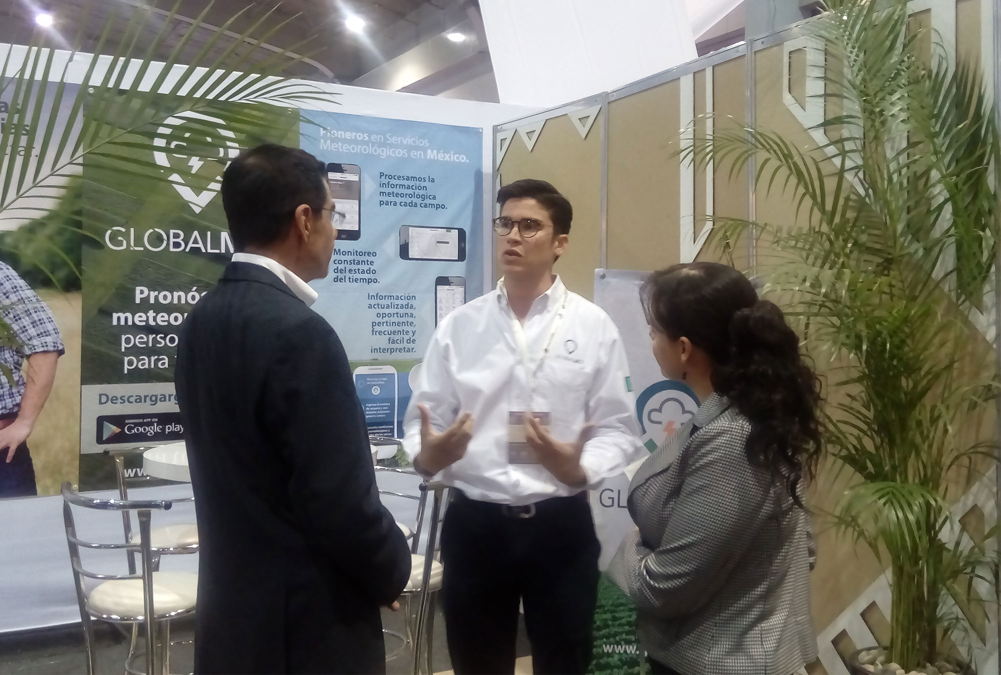 Man speaks to two judges in front of a booth with promotional materials for Globalmet