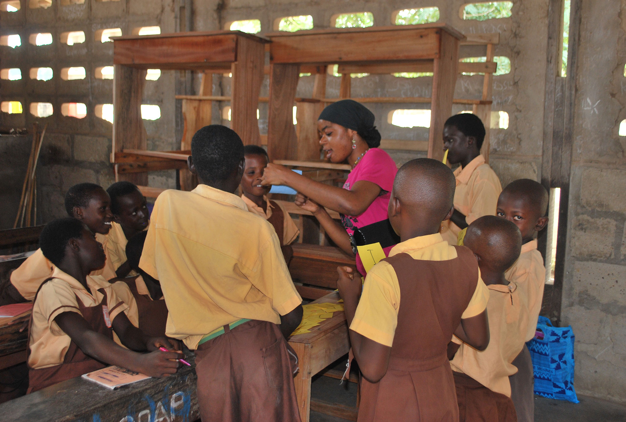 Students gather around their teacher in Ghana.