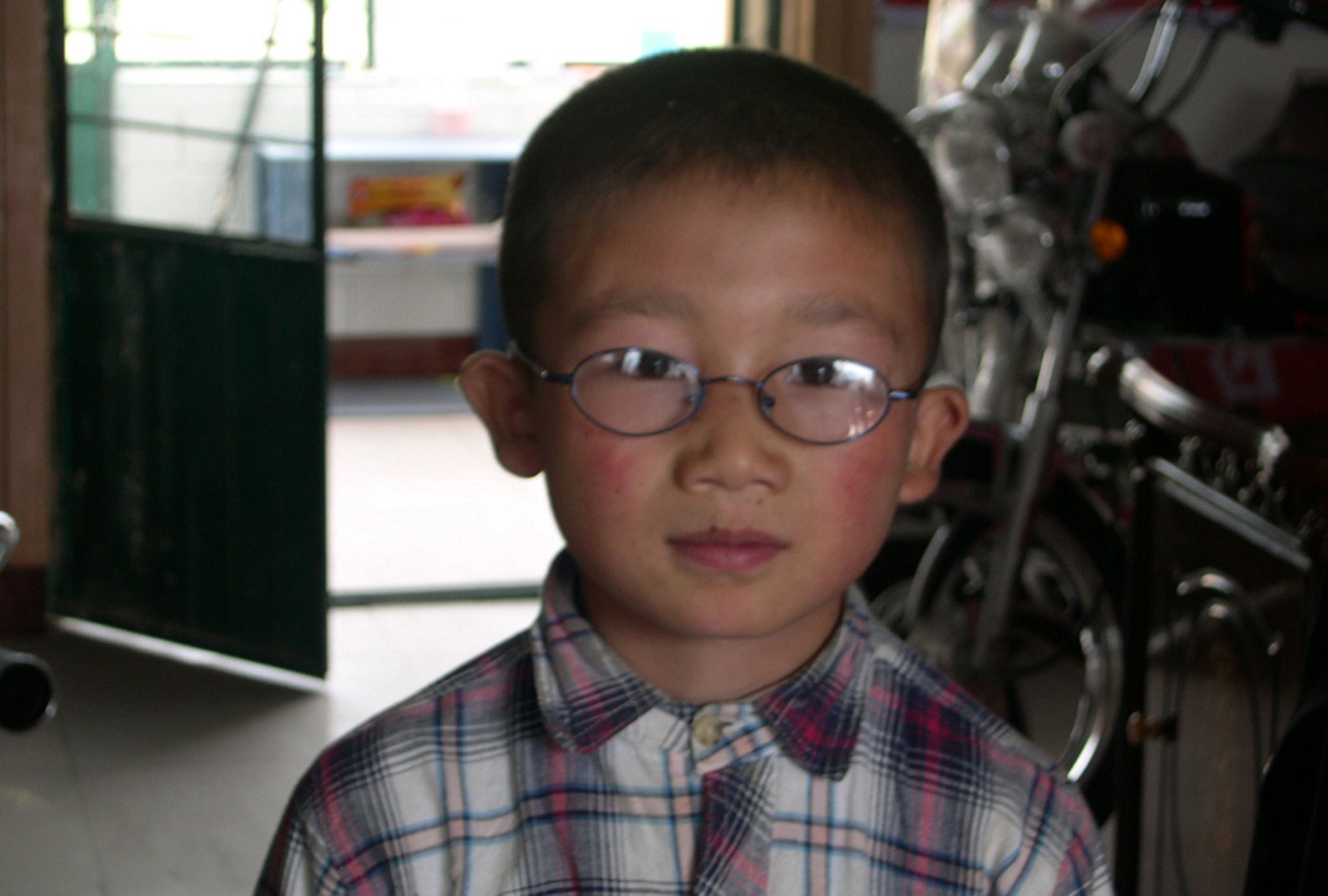 A schoolboy shows off his new glasses in Gansu Province, China.