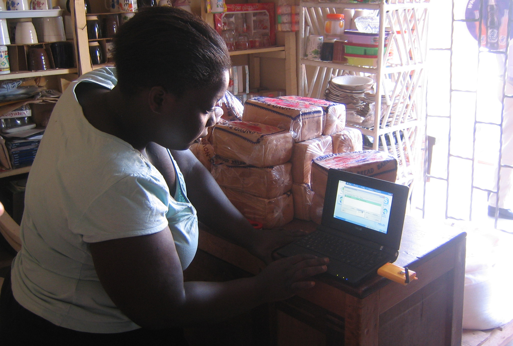 Village phone operator testing her laptop's internet access in rural Uganda