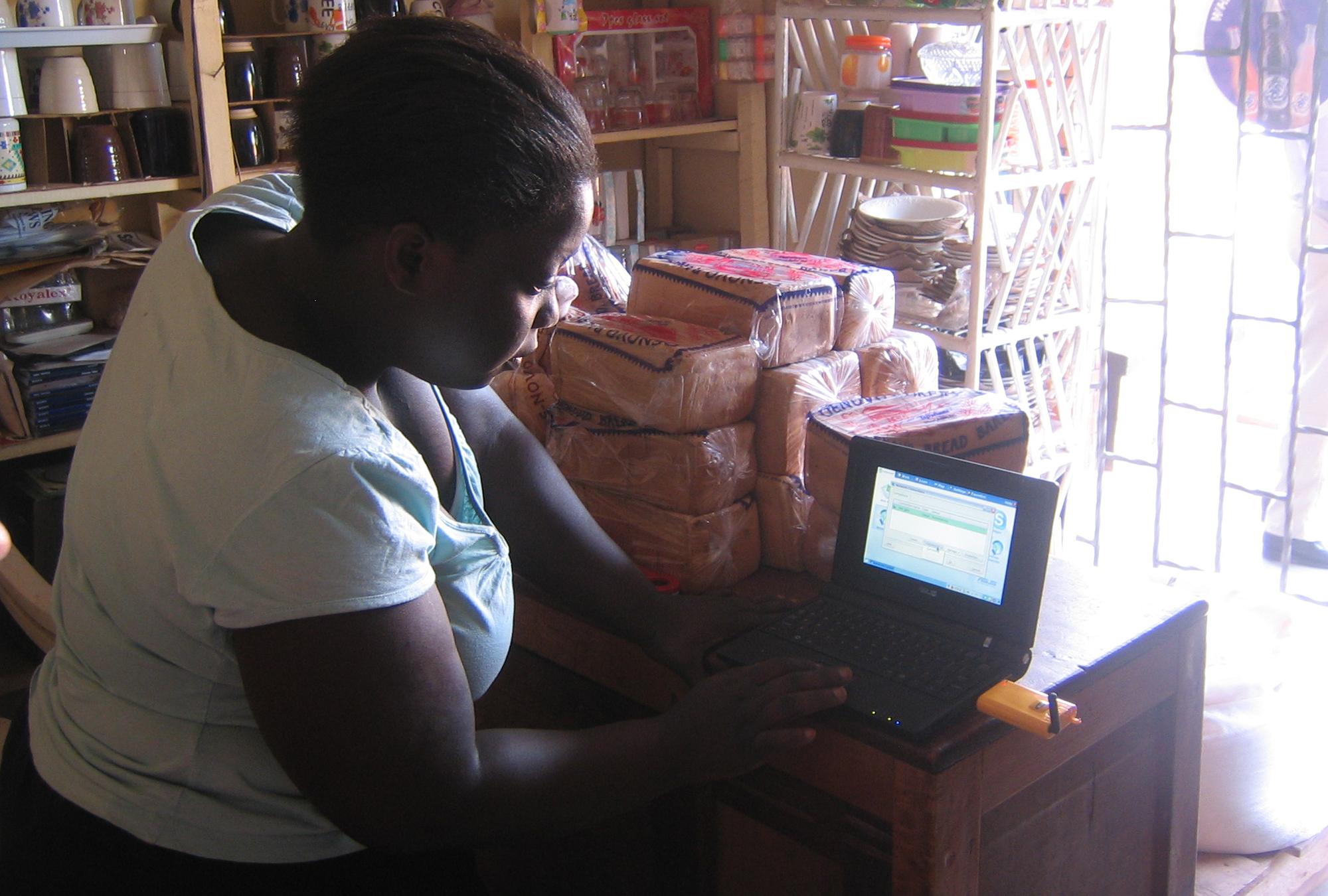 Village phone operator testing her laptop's internet access in rural Uganda