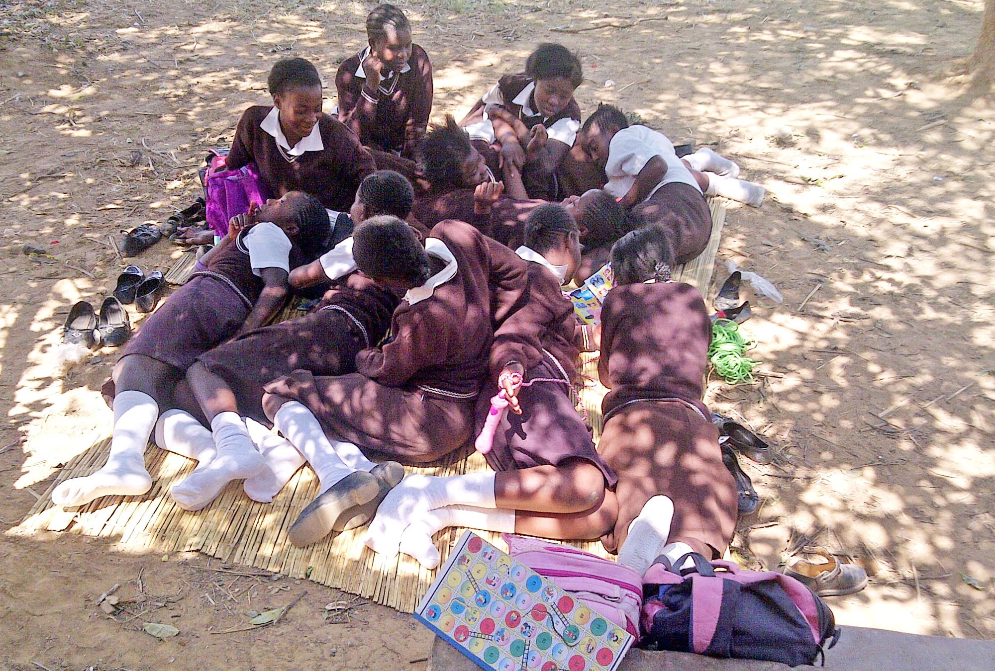 Girls in uniforms lounge outside on mat