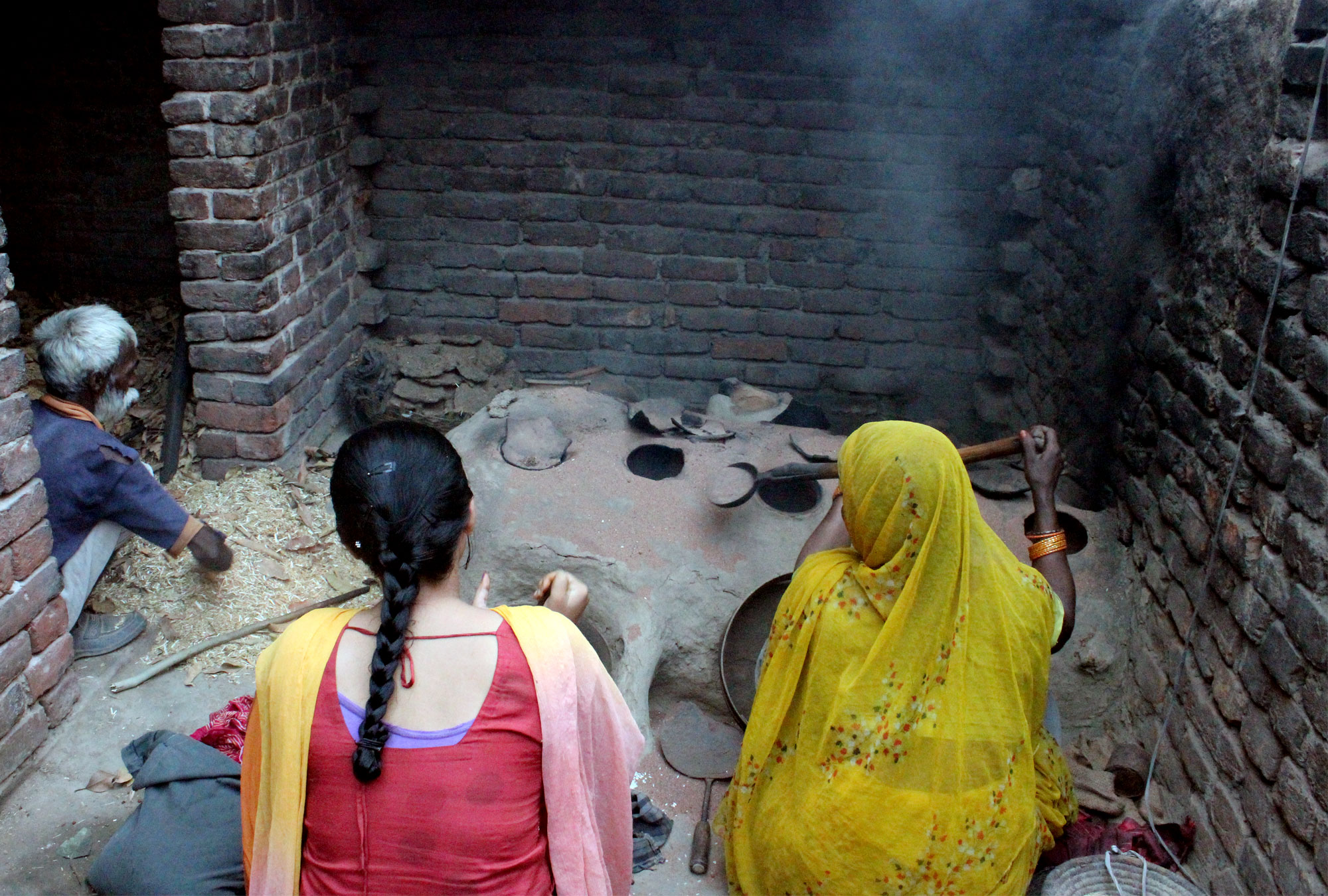 Two women sit in front of mud stove