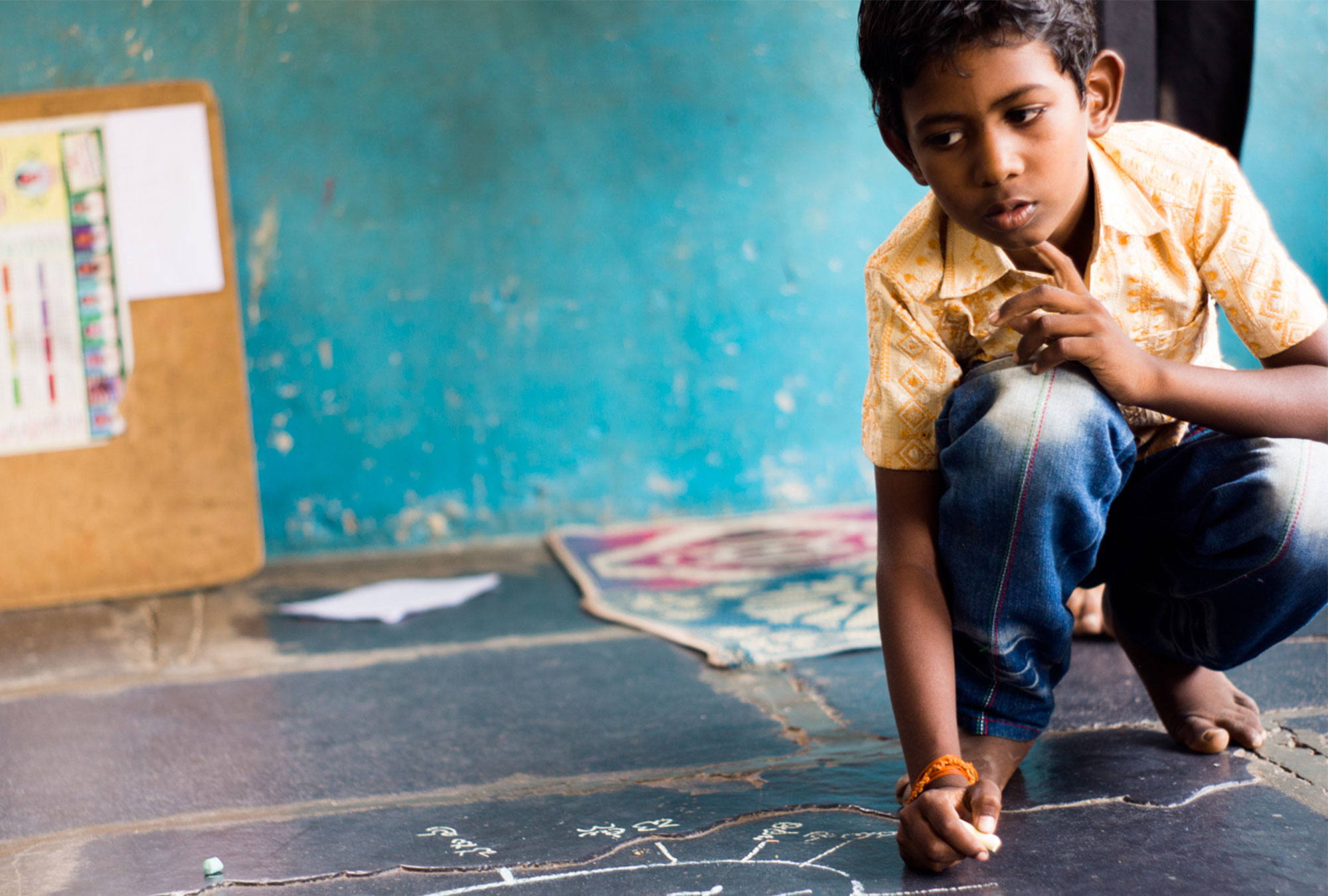 Young boy pauses in thought while writing on the floor in chalk