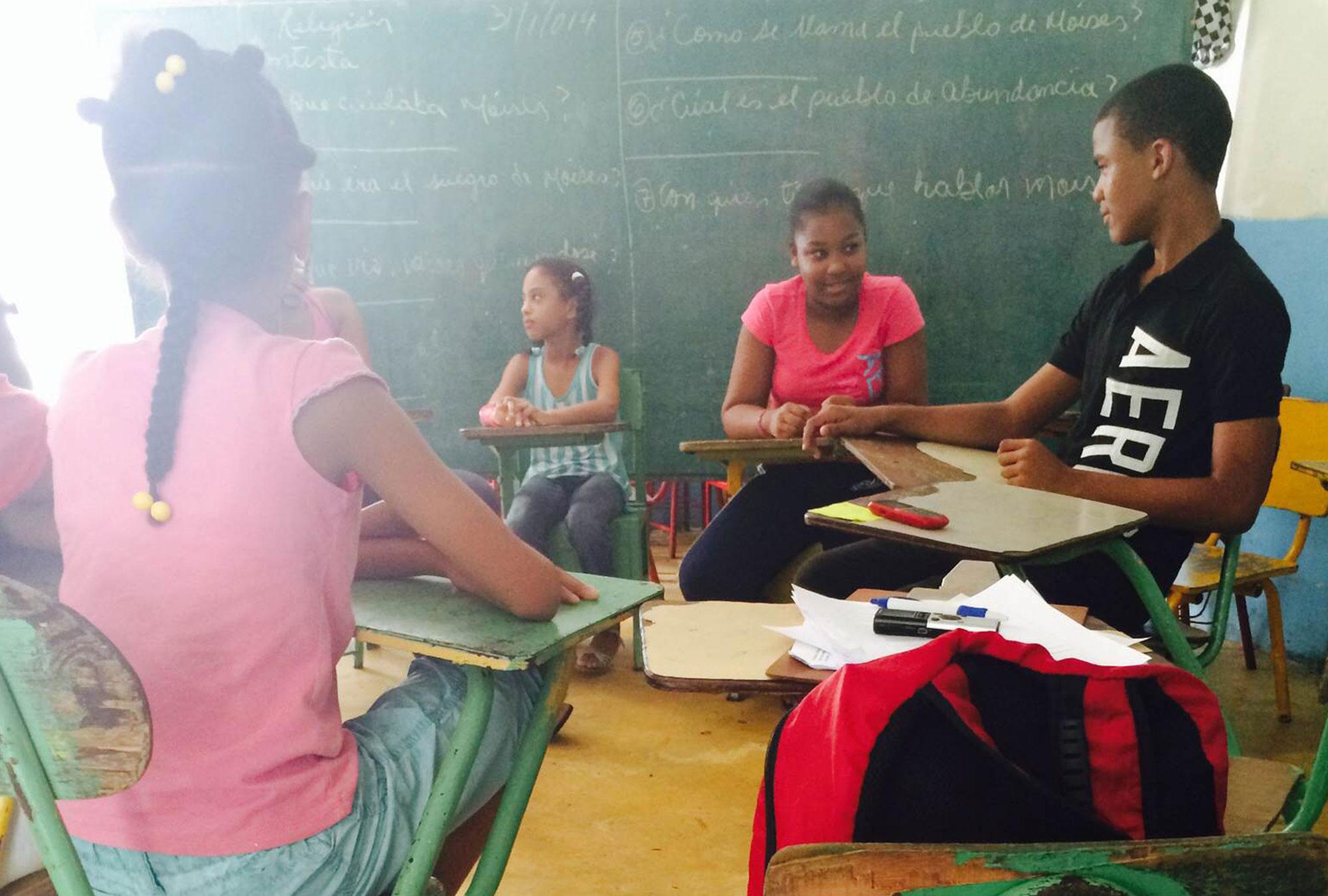 Children sit in schooldesks in front of blackboard
