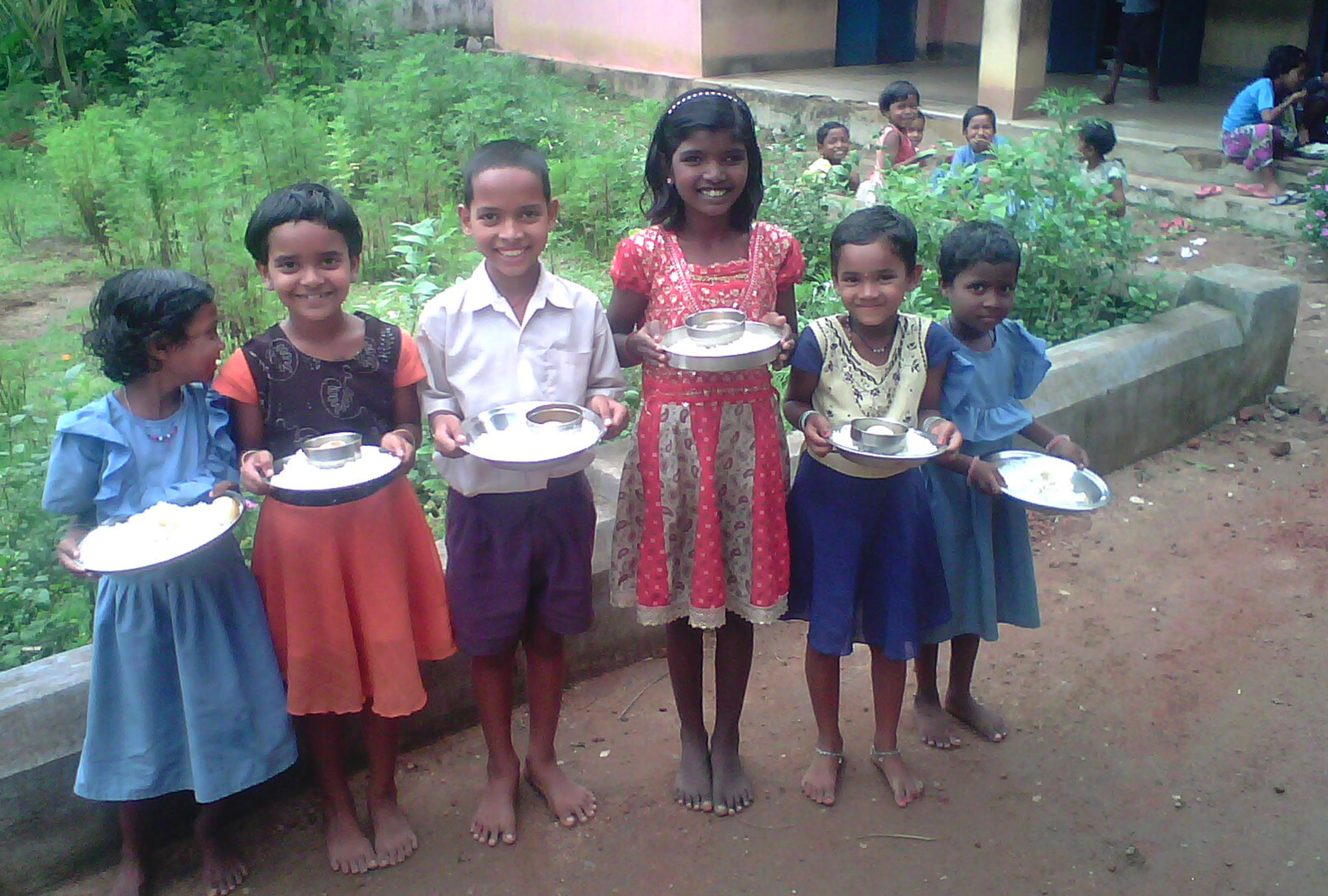 Schoolchildren in Orissa, India pose with their mid-day meals.