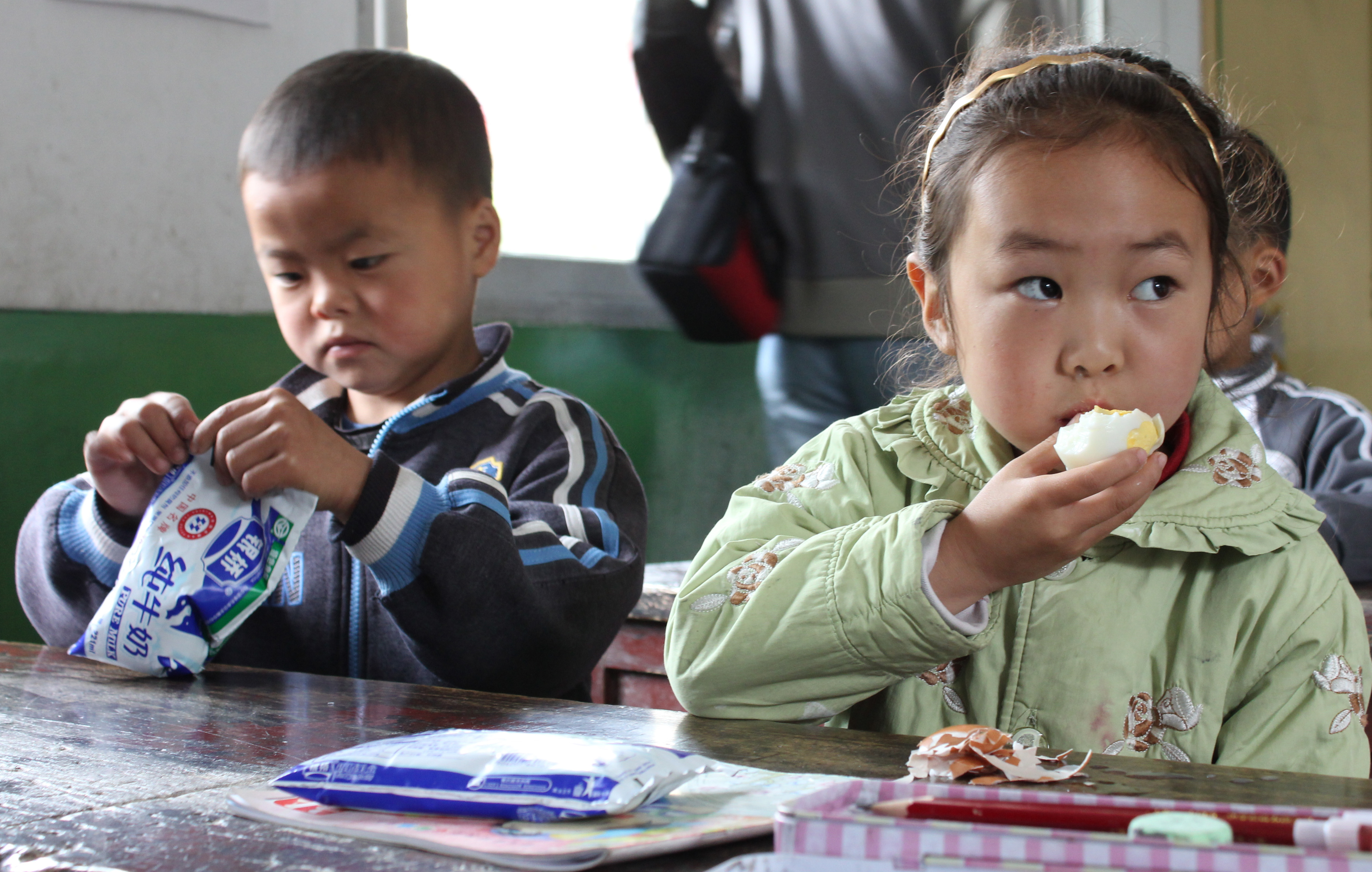 Young boy opening bag and girl eating egg