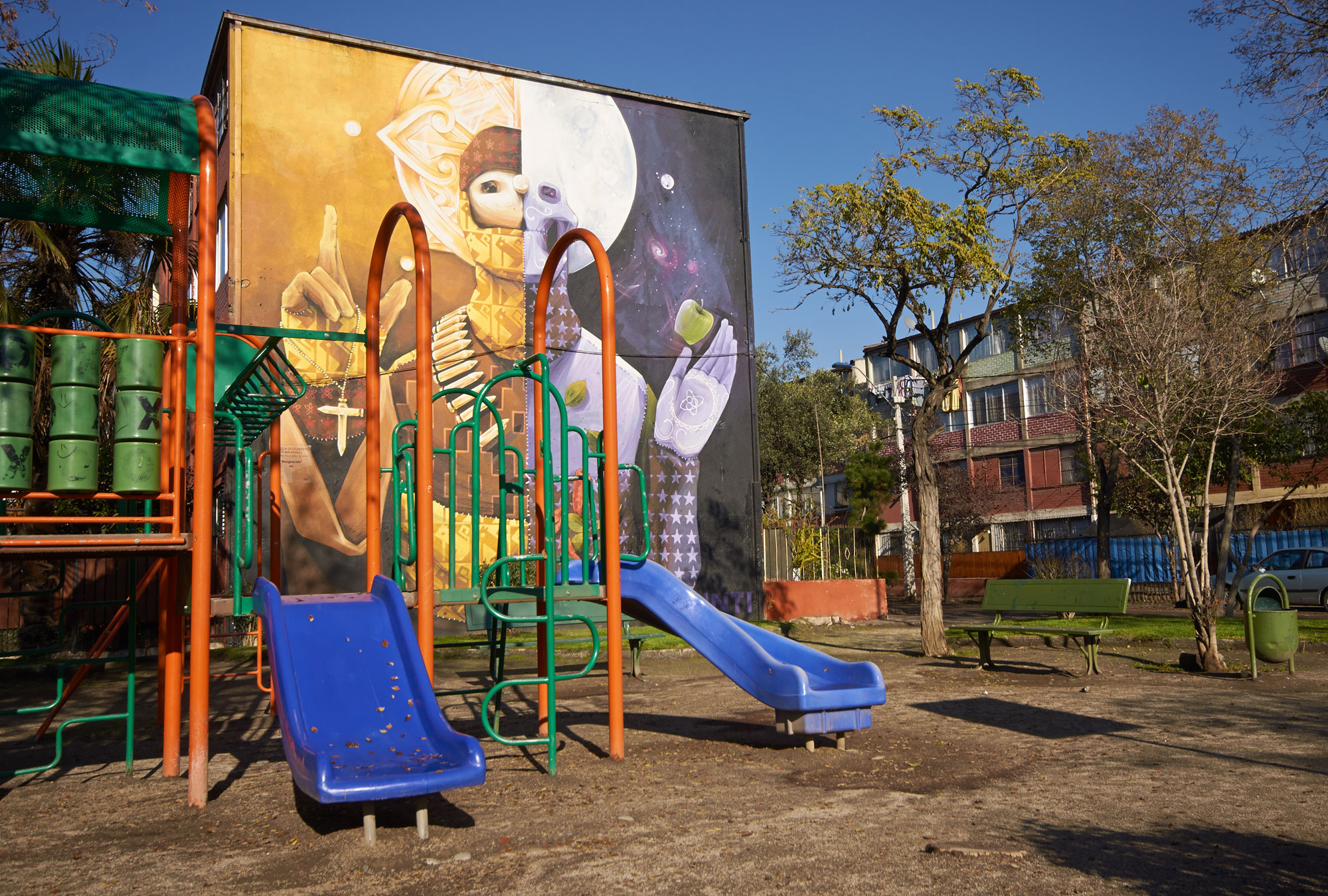 Playground in front of building with colorful mural