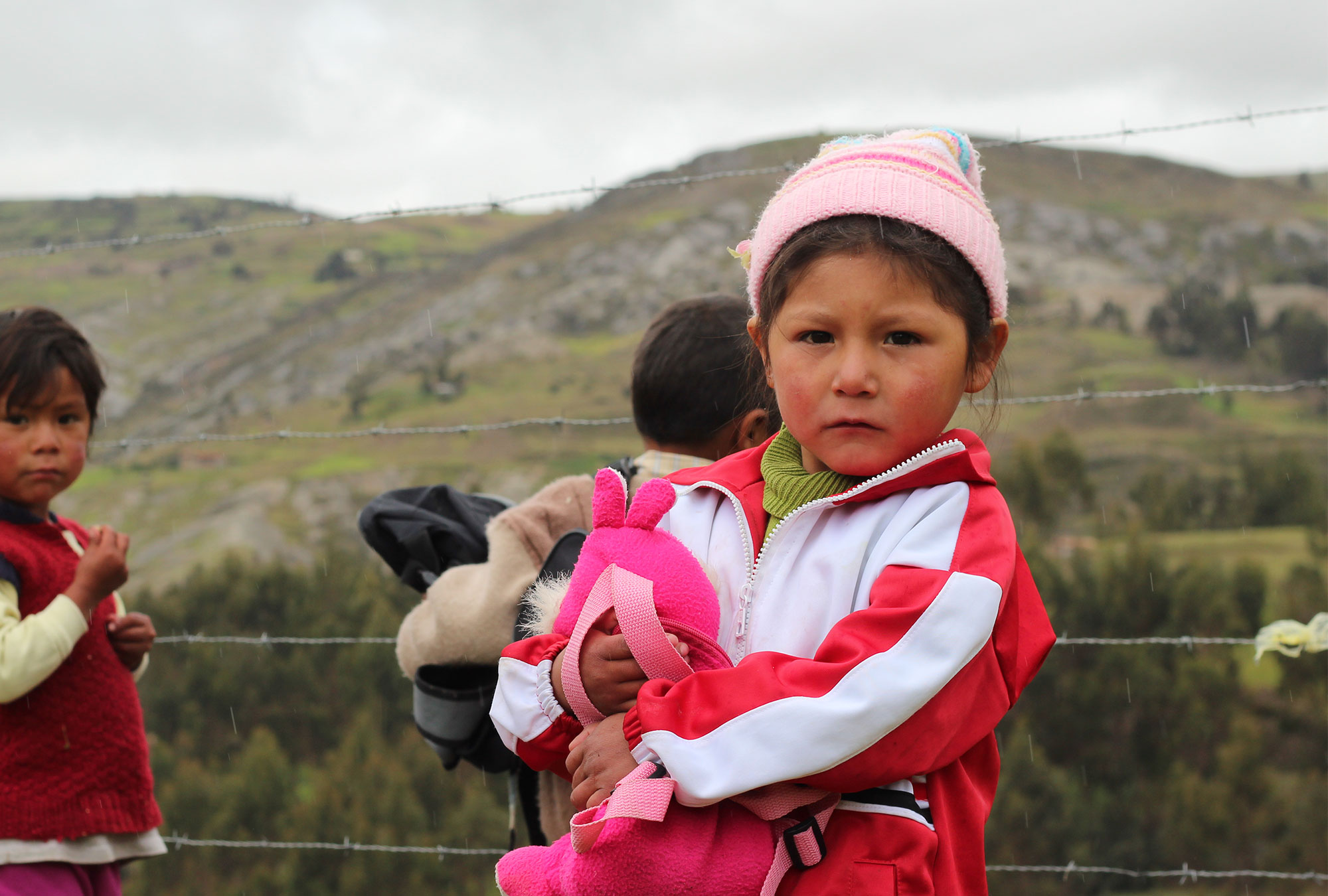 Young girl in pink jacket and hat outside in rural Peru