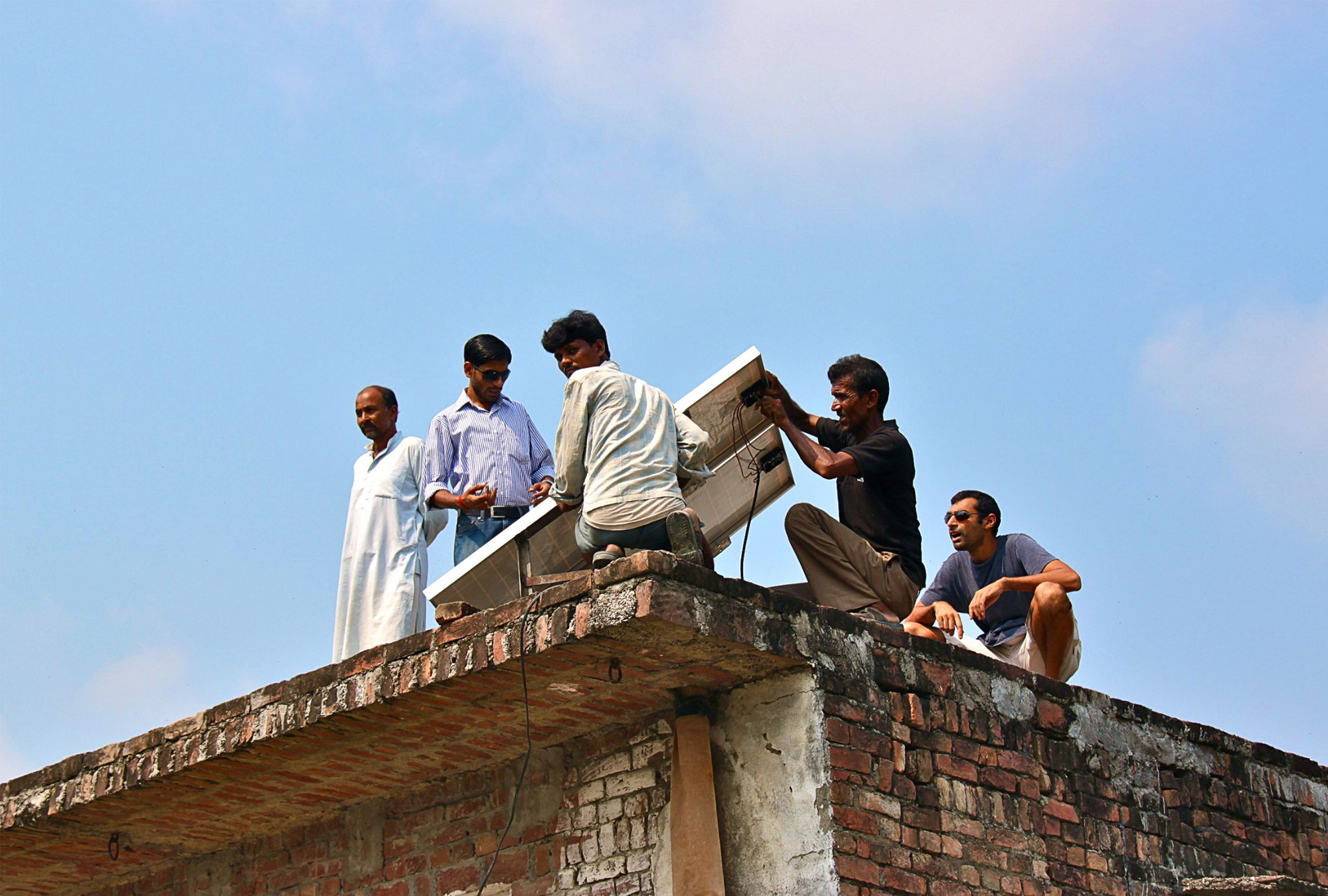 Group of men on the roof of a building installing solar panel