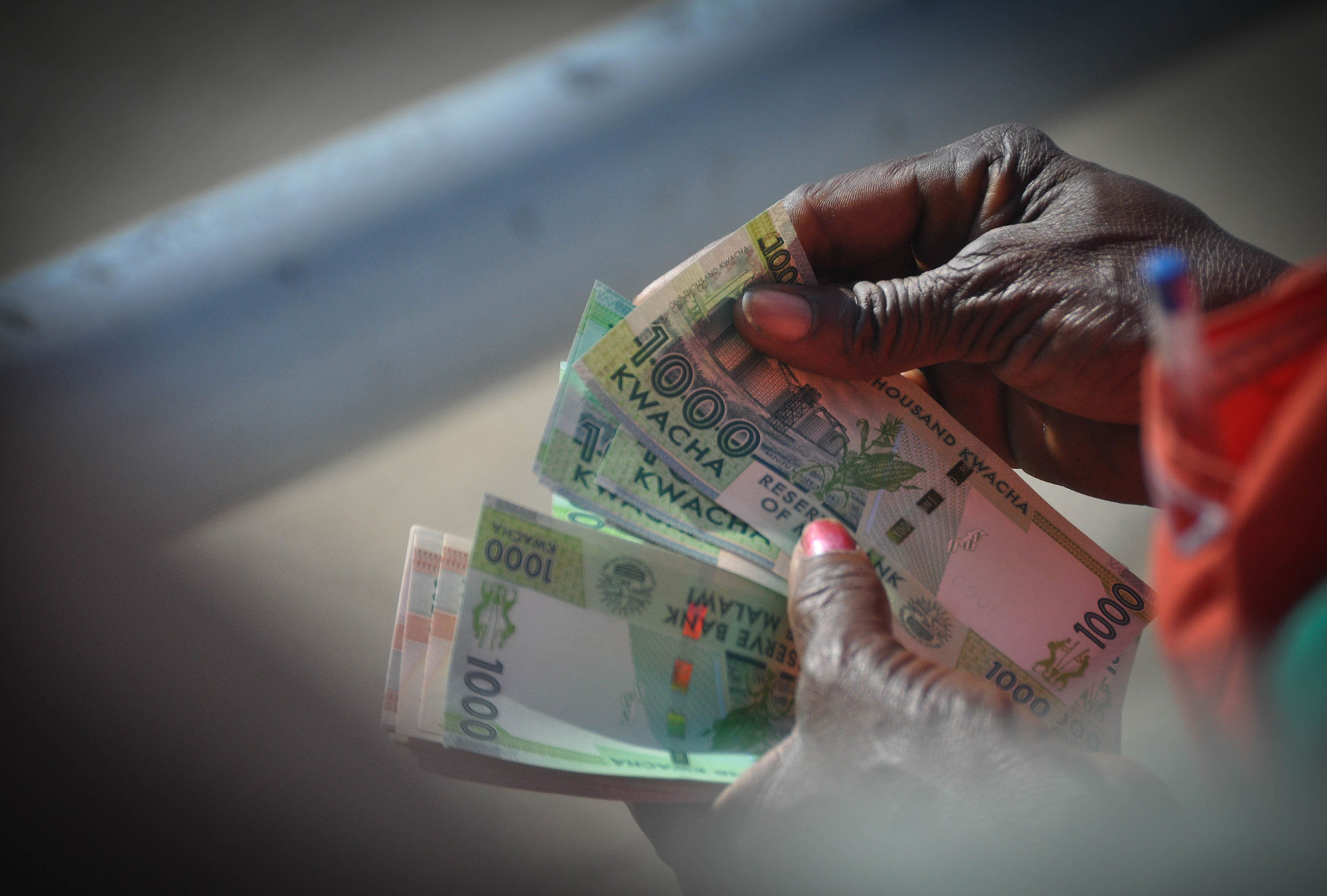 Person holds Malawian currency (Kwacha)