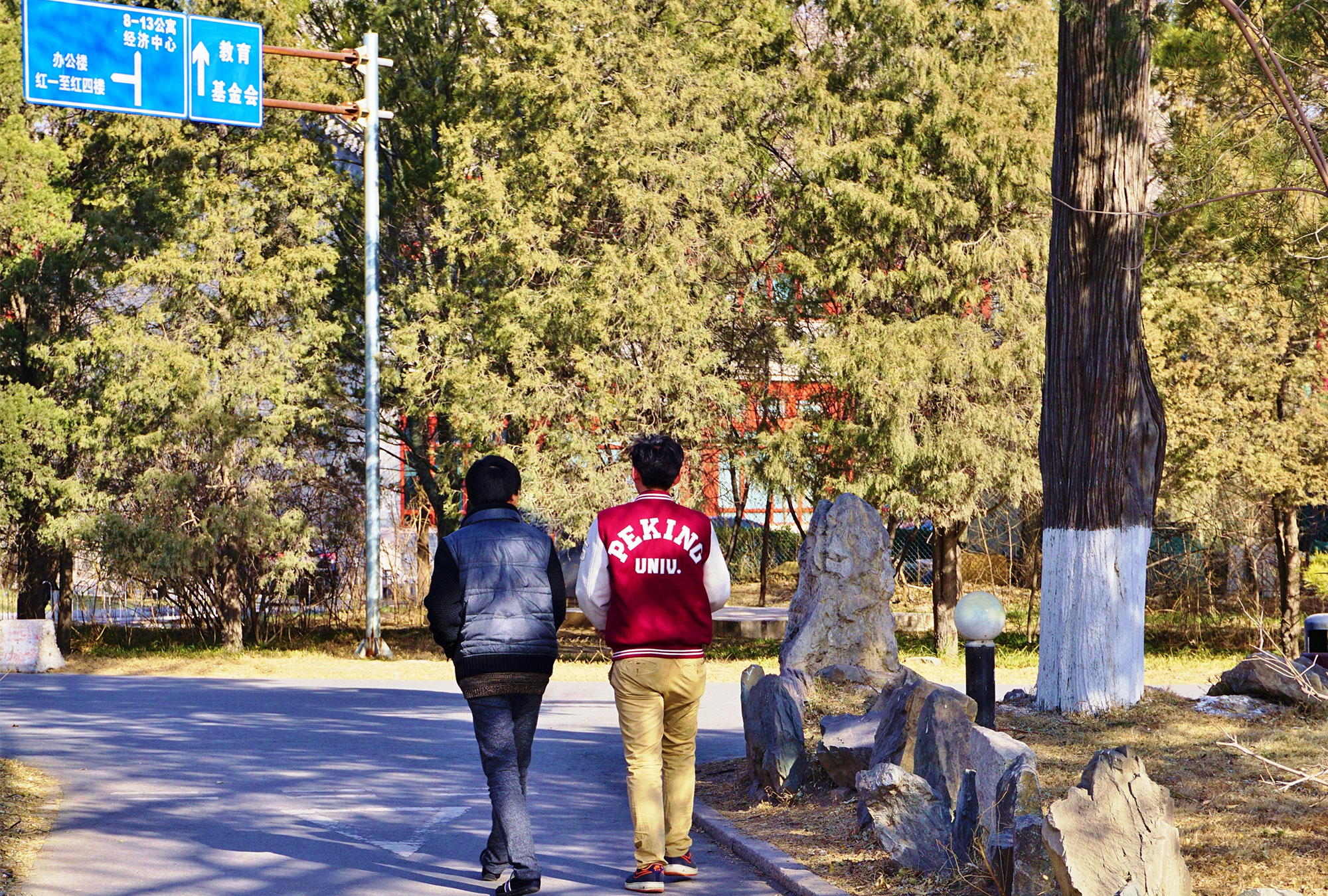 Two students walking: one's jacket reads 'Peking U""