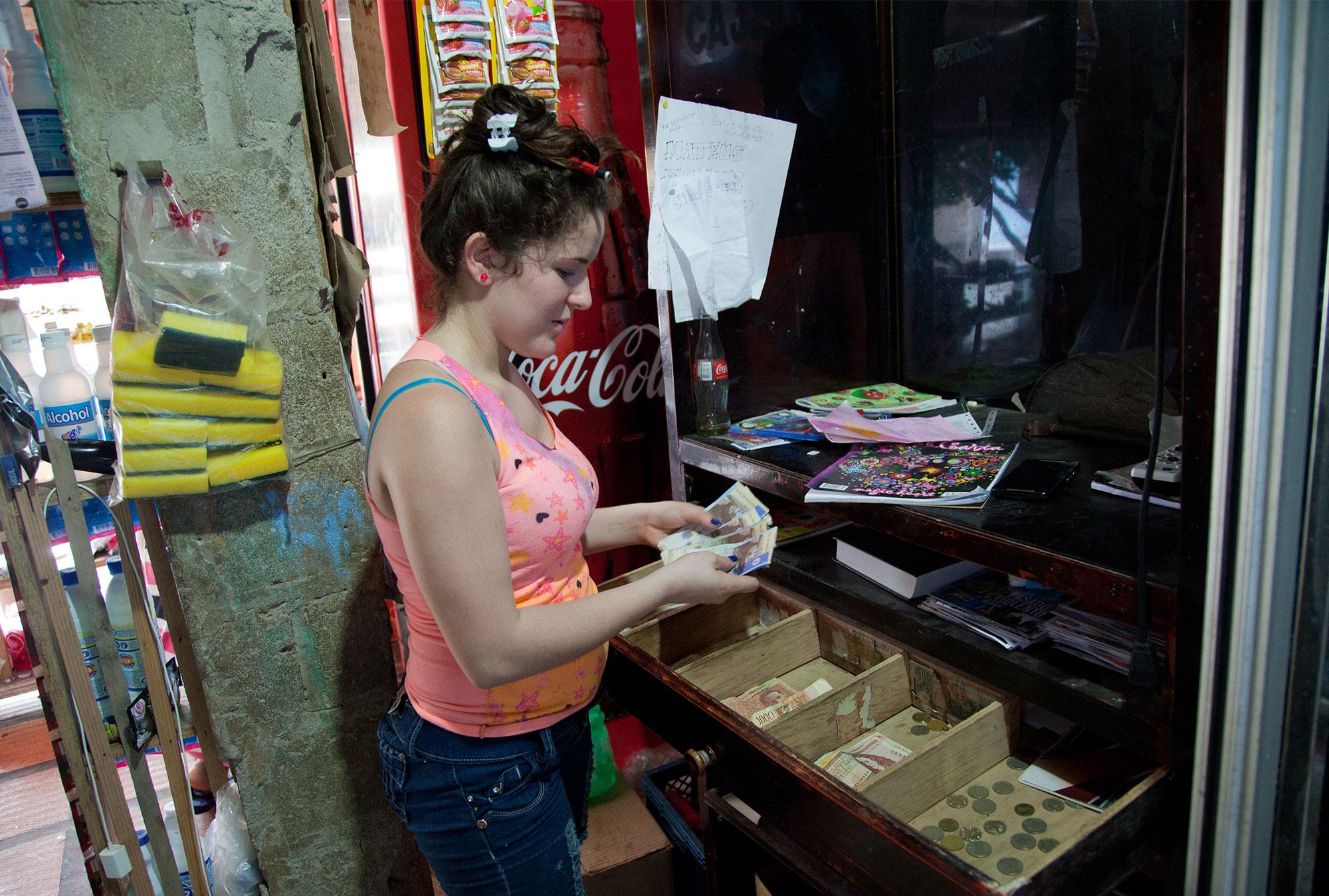 Woman counts money in register