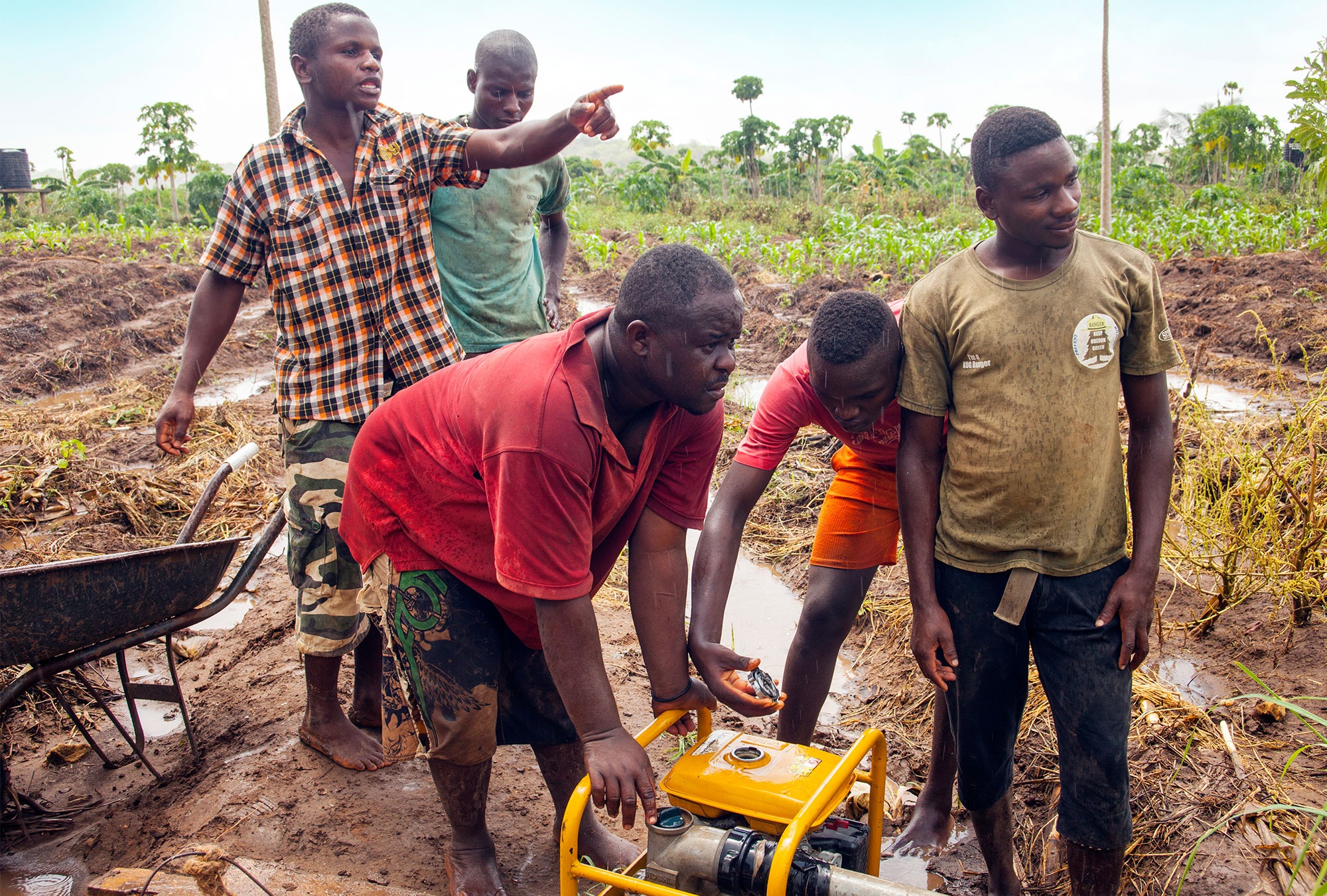 Five men stand in a field in the rain operating a small pump machine