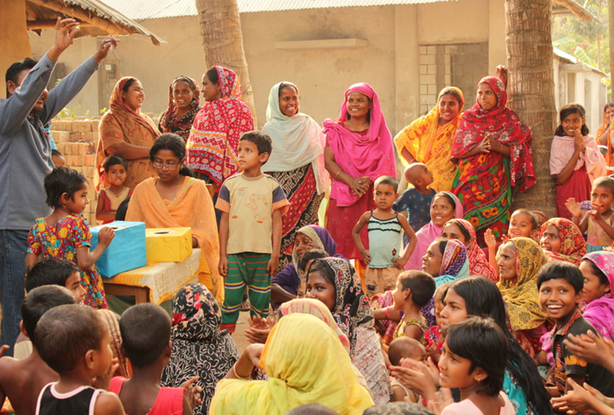 Crowd of women in bright saris watch man hold up token from cardboard box