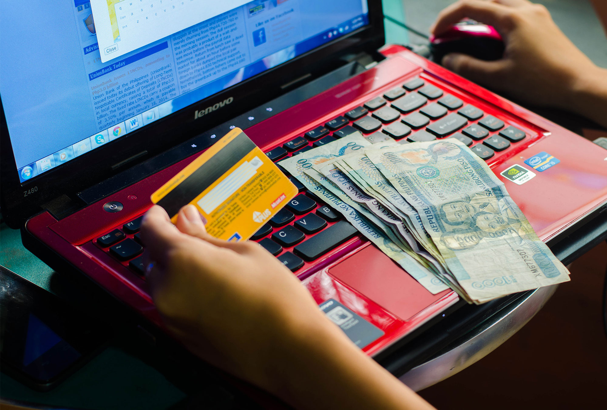 Person works on laptop with Philippine currency and bank card