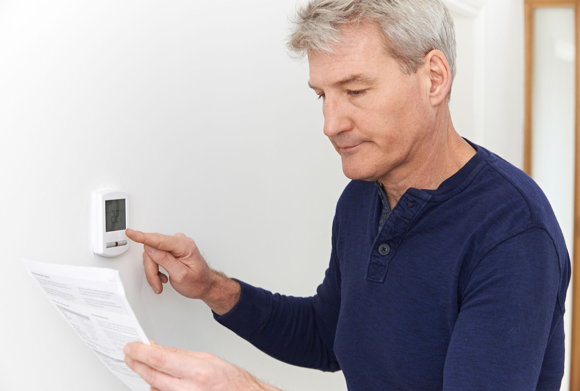 Man adjusts thermostat