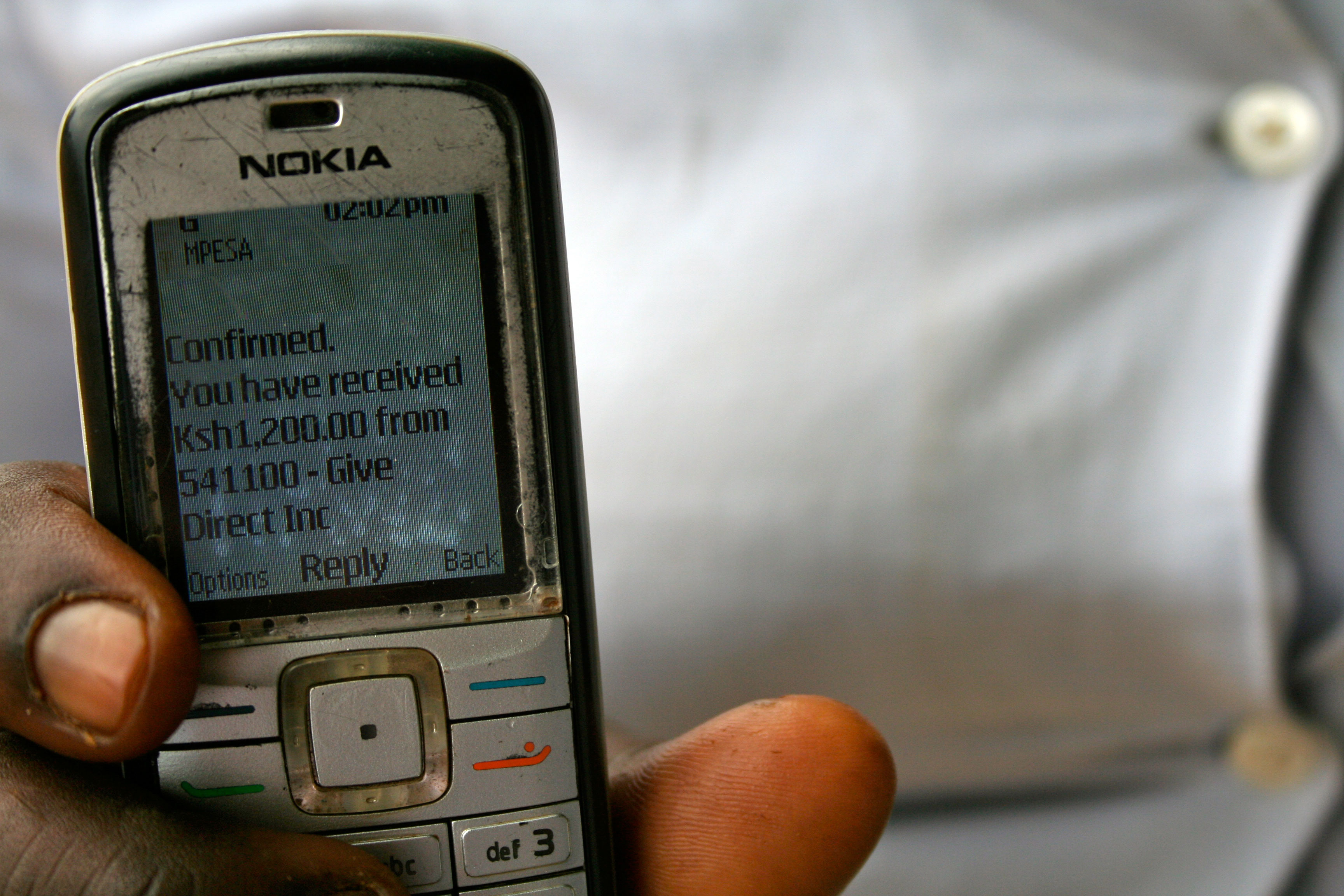 Man holds up phone showing message of mobile money received from GiveDirectly
