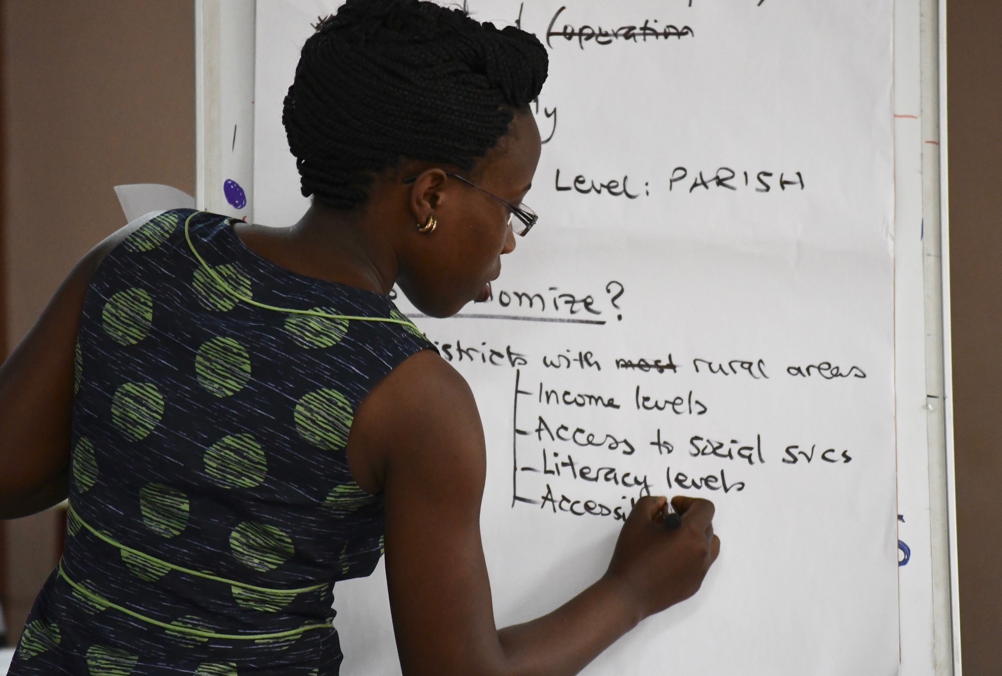 A woman writes on the board during the Evaluating Social Programs course in Kampala in 2018.