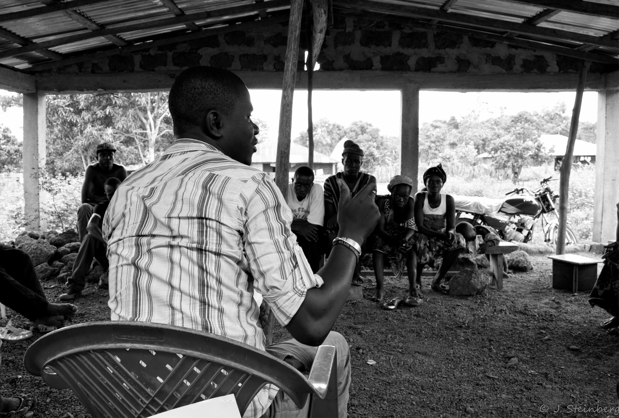Man leads a discussion under an outdoor meeting tent