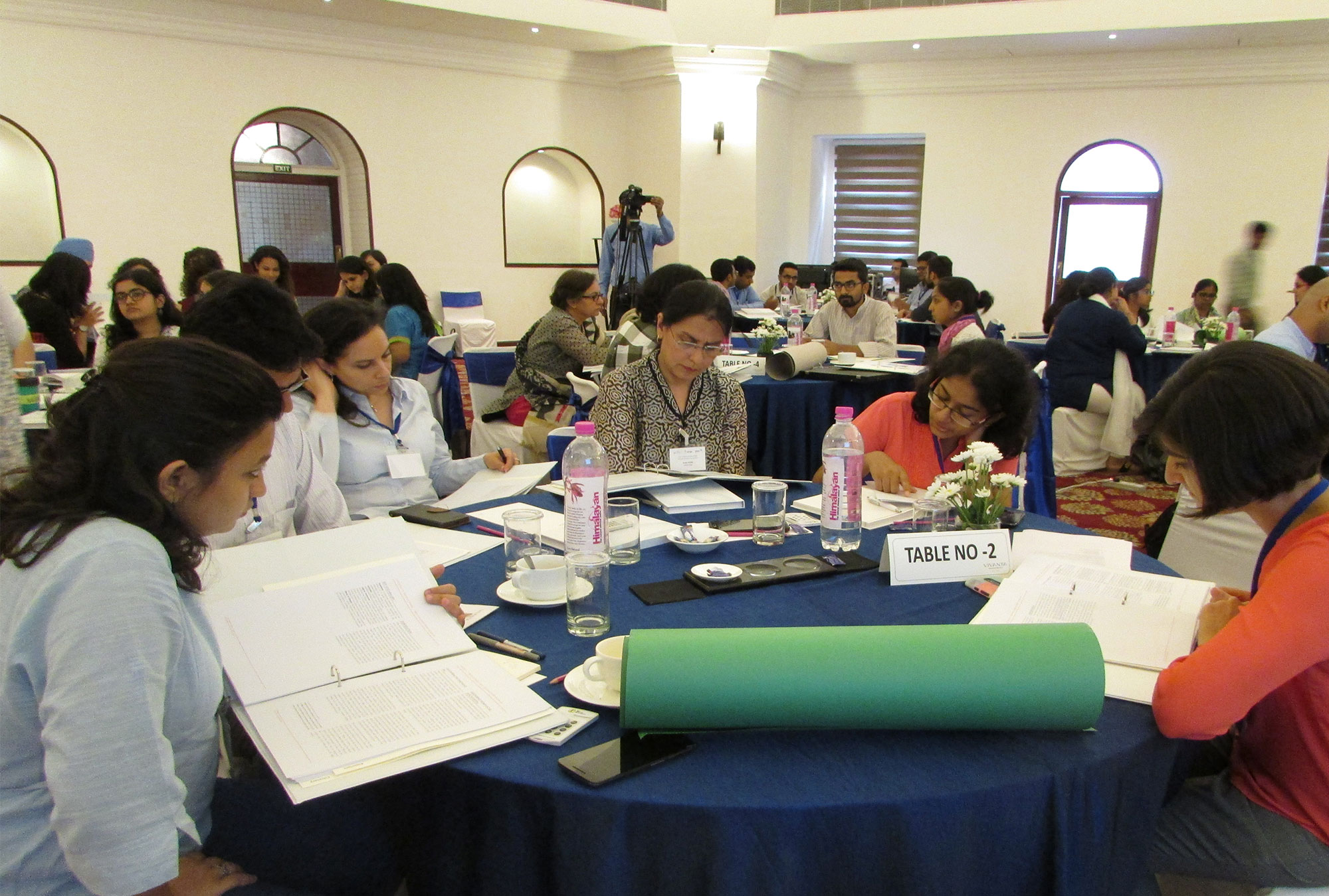 Participants at training sit around round table