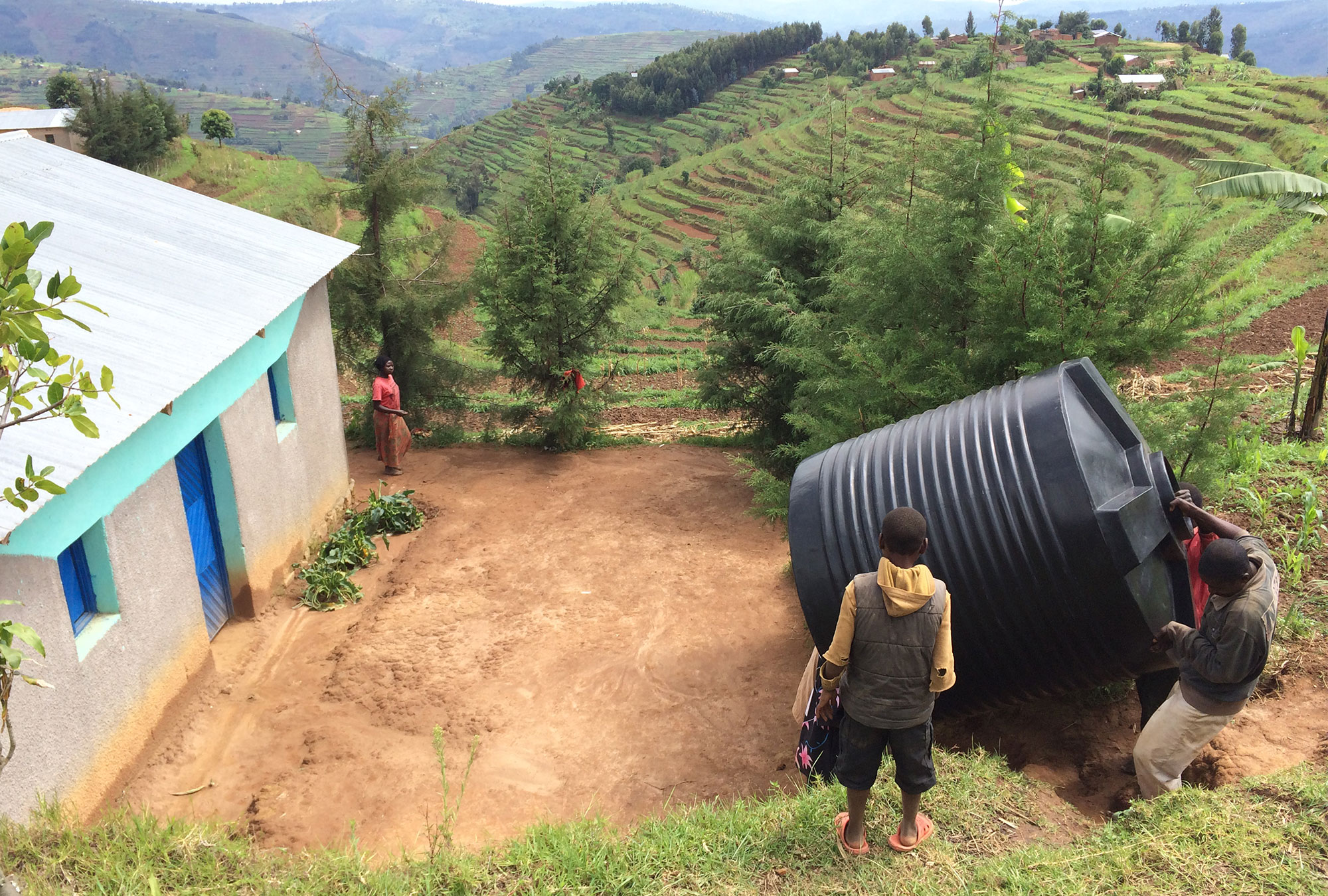 People carry large water tank up a hill in terraced agricultural landscape