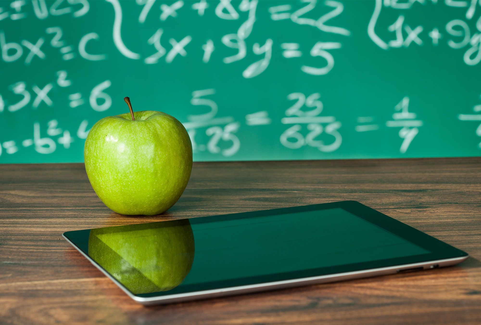 iPad and an apple in front of a chalkboard