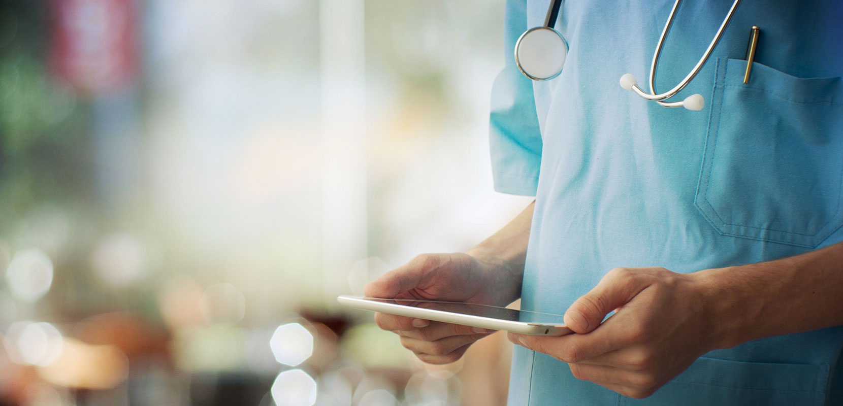 A doctor holds an tablet in his hands.