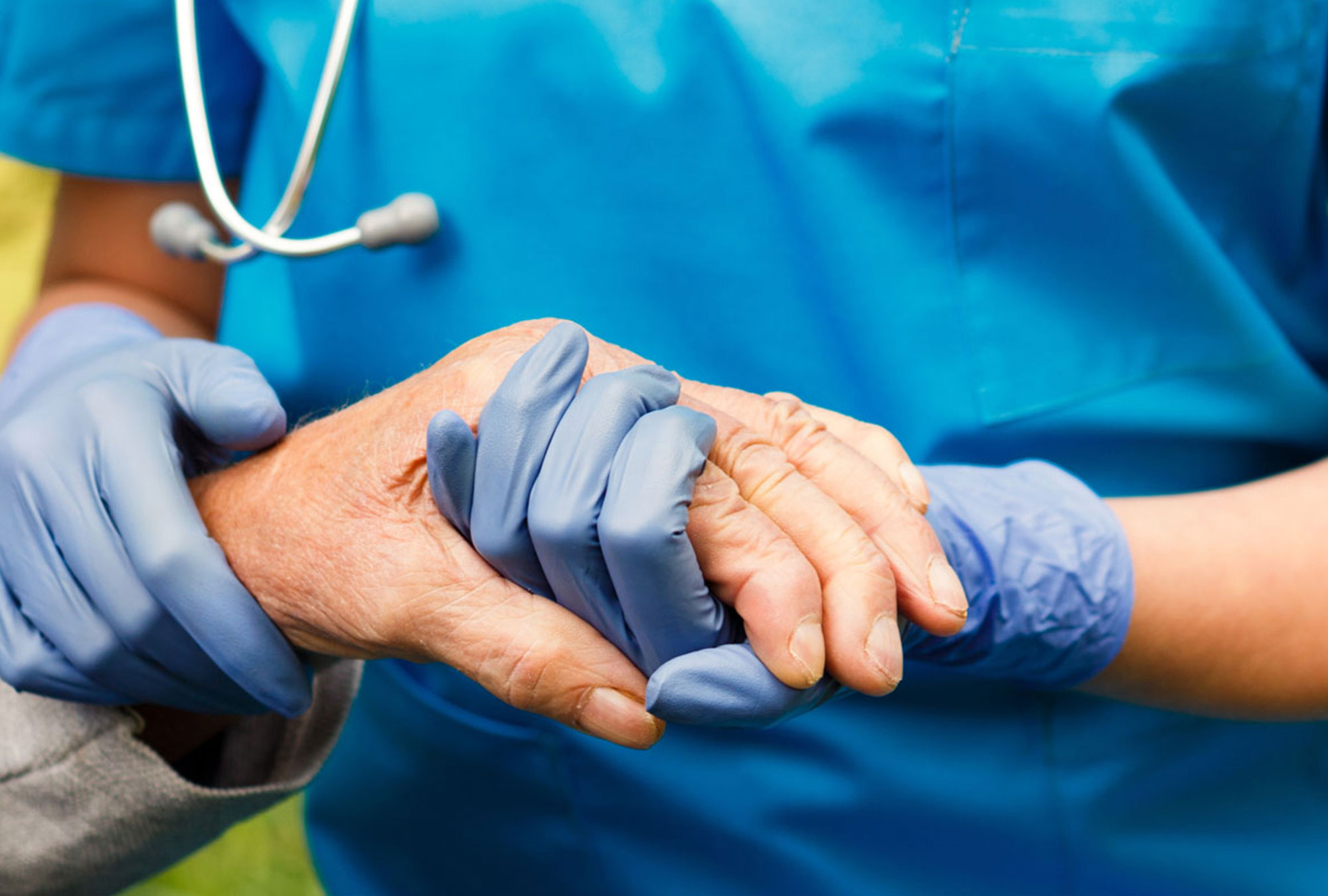 Doctor's gloved hands holding patient's hand